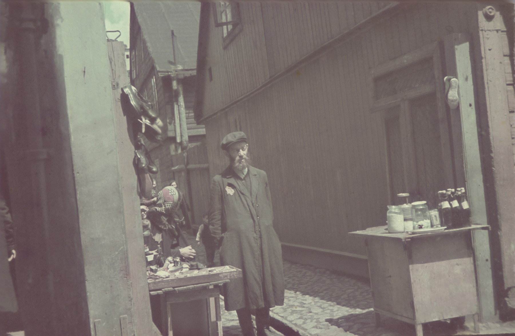 A bearded, religious, Jewish vendor stands by his stall in the Lodz ghetto.