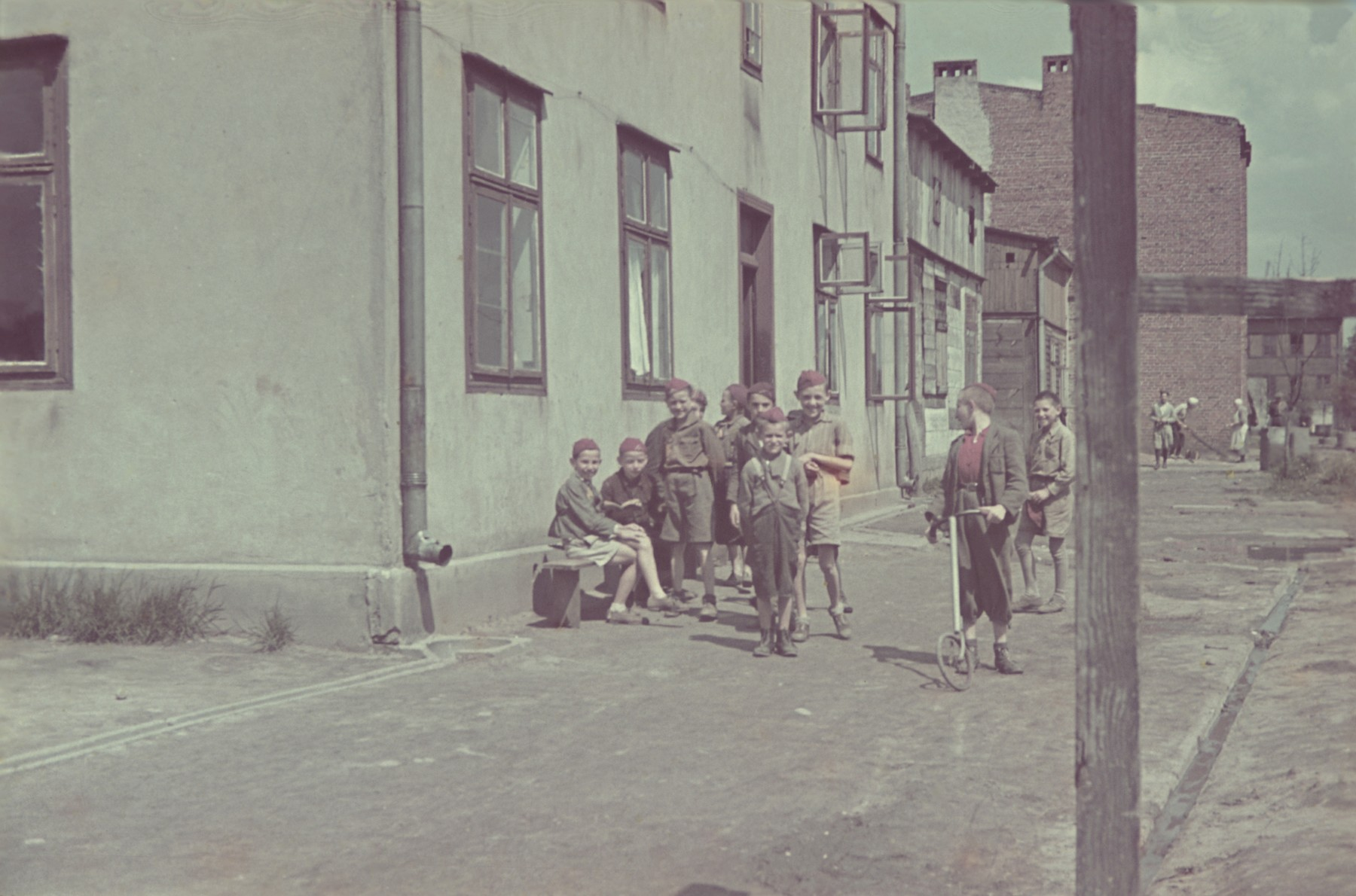 A group of boys, one with a scooter, stand on a street corner in the Lodz ghetto.