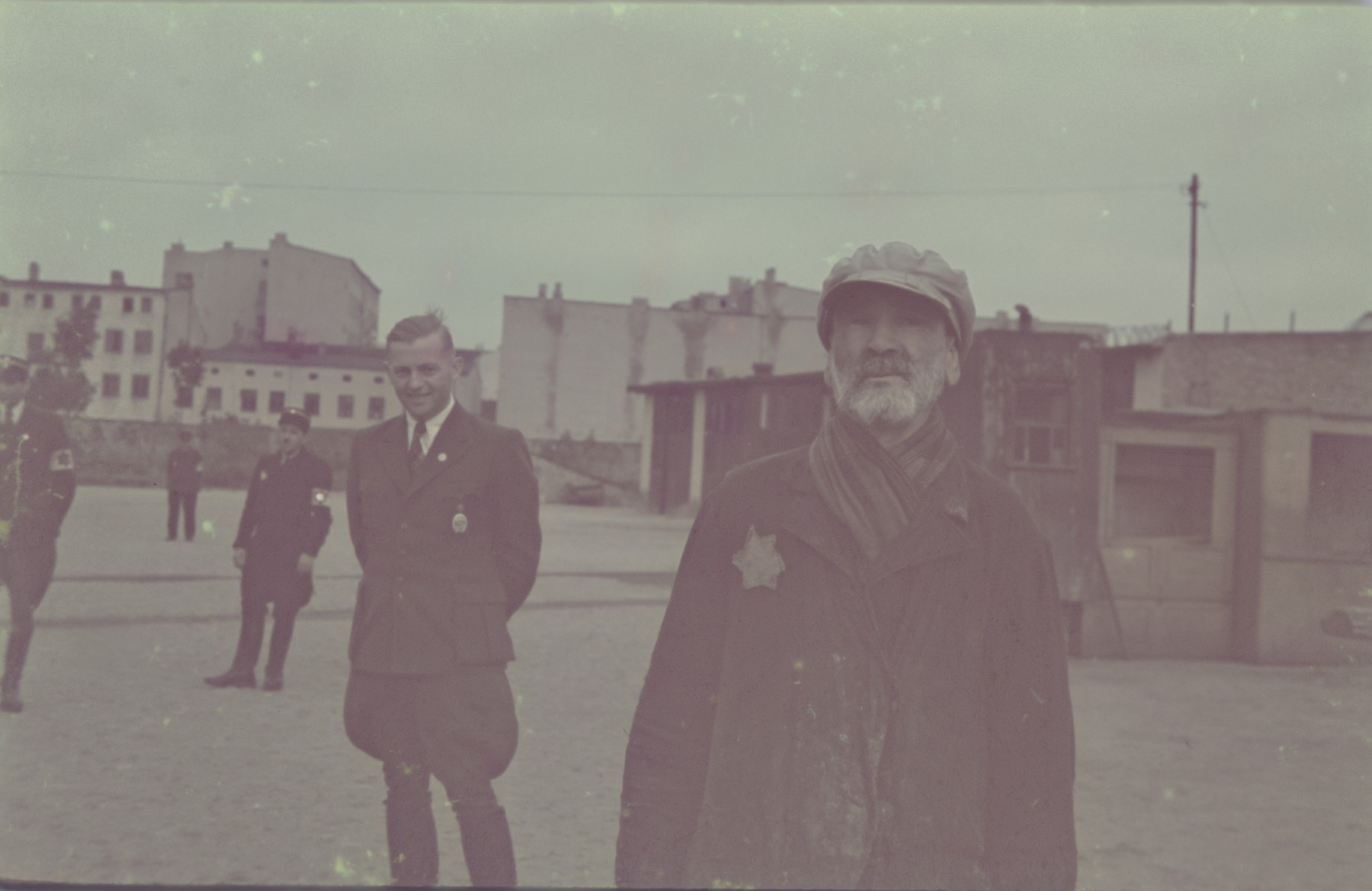 Hans Biebow, German head of the Lodz ghetto administration, observing an elderly and destitute Jew in the ghetto.