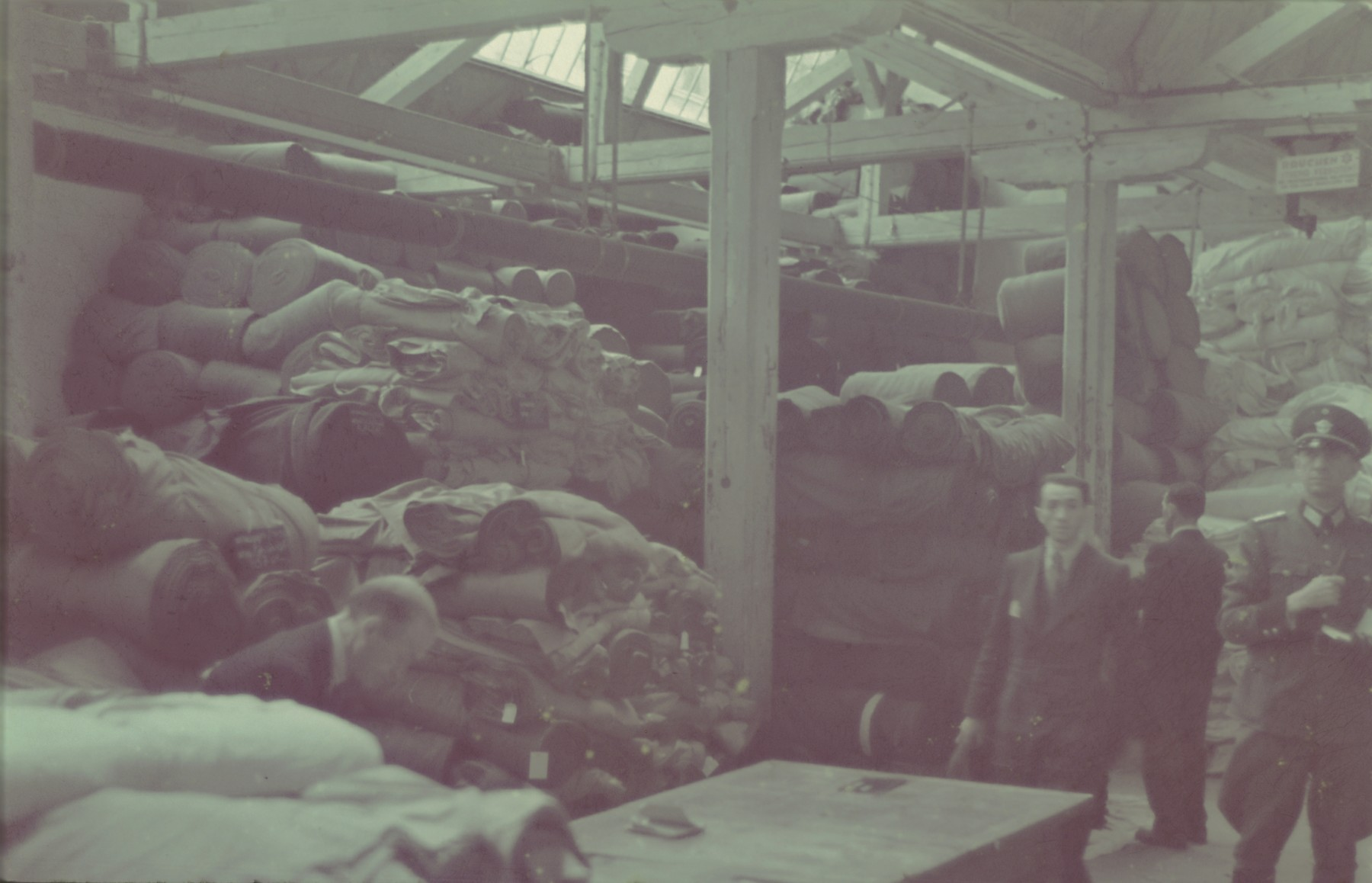 "A German official inspects the textile storeroom in the Lodz ghetto.  Original German caption: ""Getto, Litzmannstadt, Lager fur textilien"" (textile warehouse), #194."
