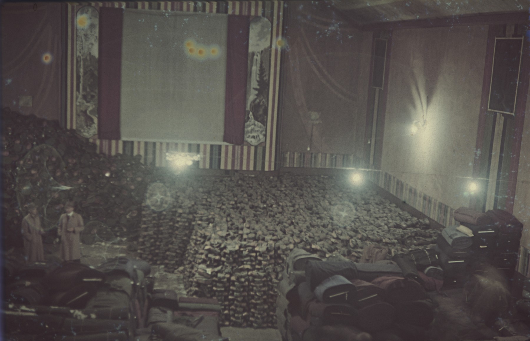 """Piles of supplies, textiles and material are piled up in a former cinema.  Original German caption: """"Lager in einem Kino"""" (warehouse in a cinema)."""