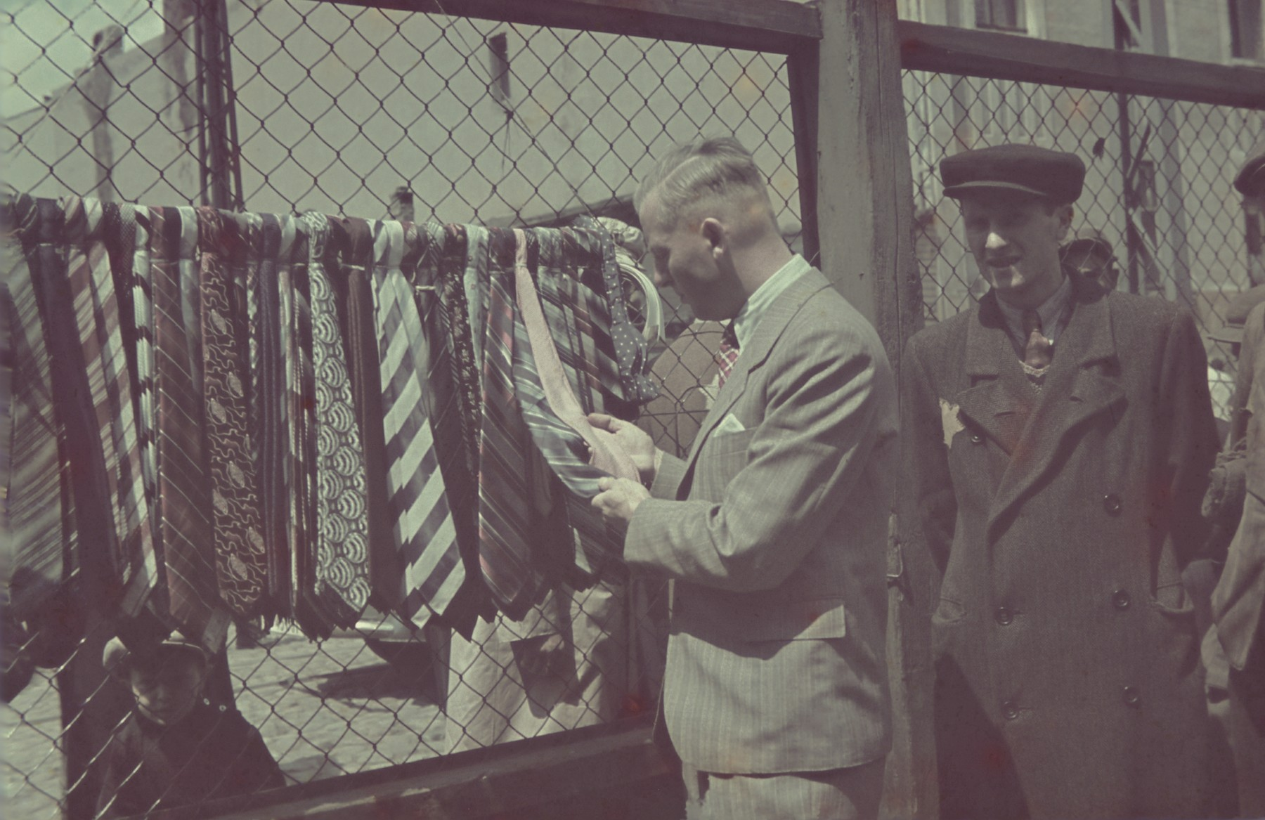 Ghetto administrator, Hans Biebow examines some ties for sale in the outdoor market of the Lodz ghetto.