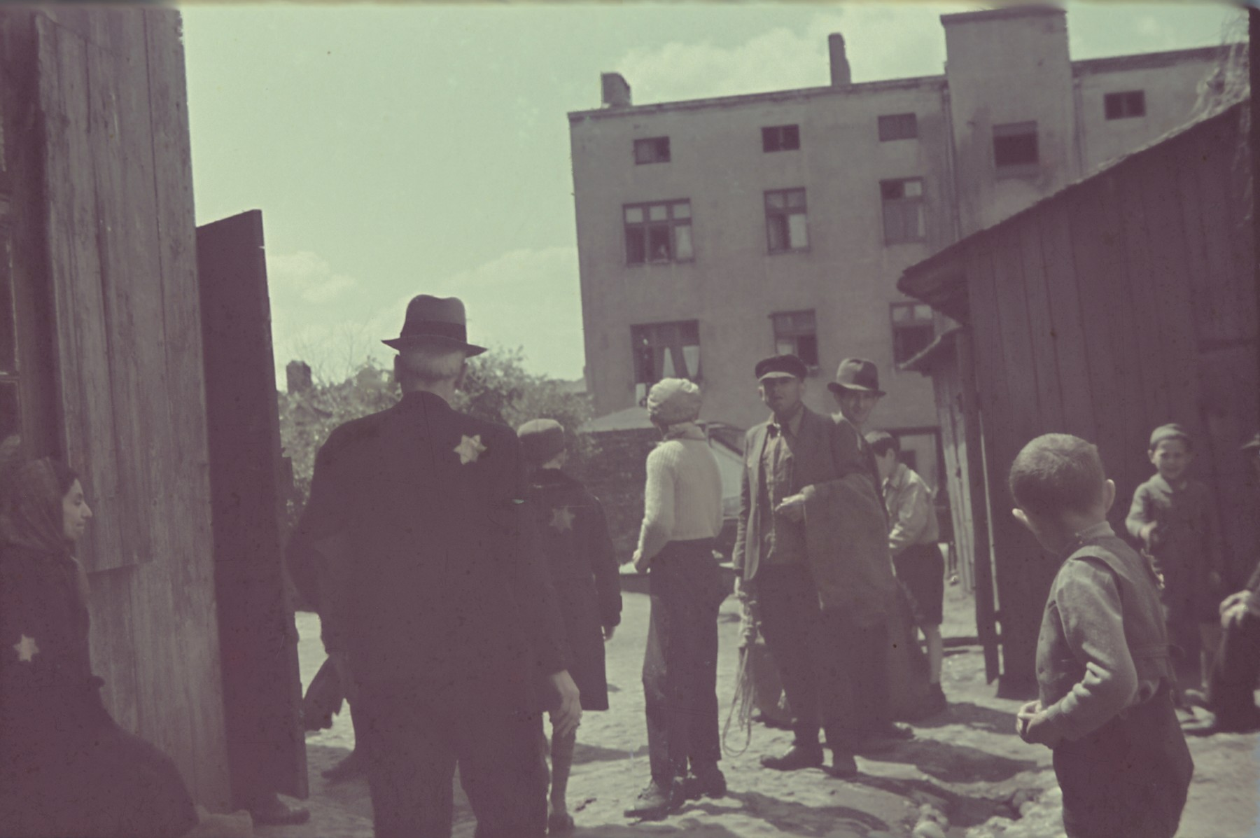 A group of ghetto residents congregate on a street of the Lodz ghetto.