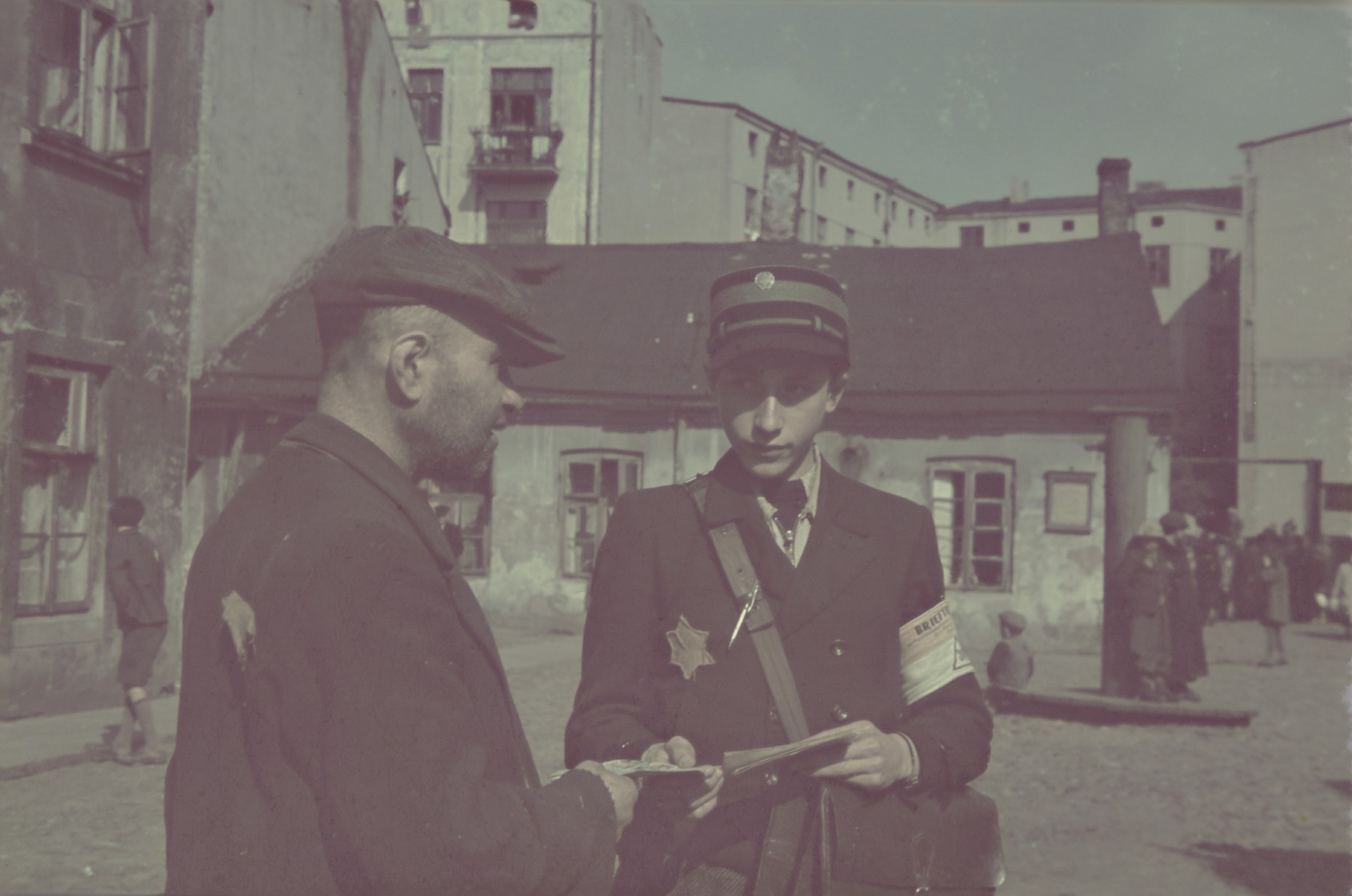 Izak Lewkowizc, a young ghetto postman delivers mail or ration cards to the ghetto resident.