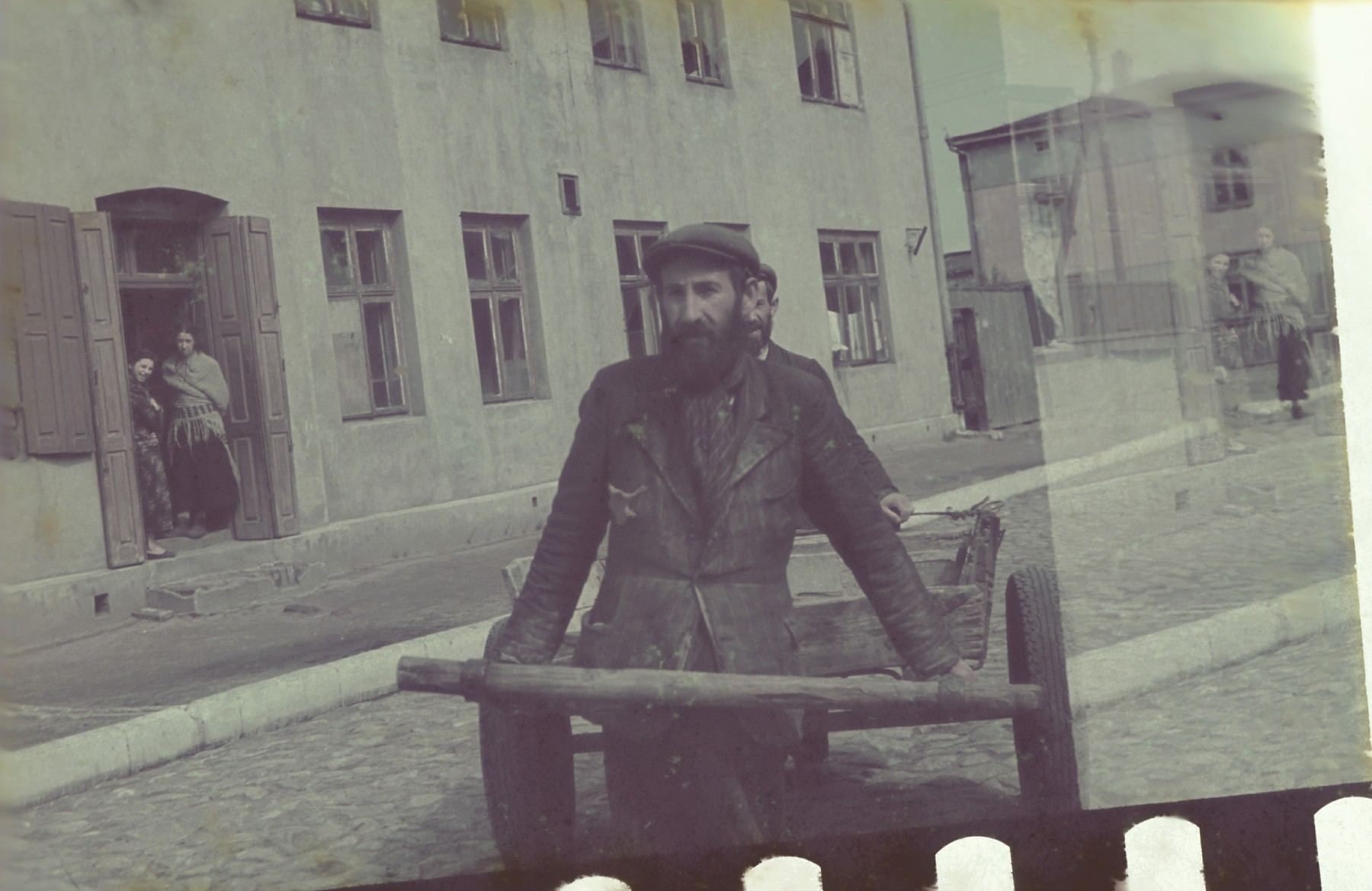 A bearded member of the transportation crew pulls a wooden cart through a street of the Lodz ghetto.