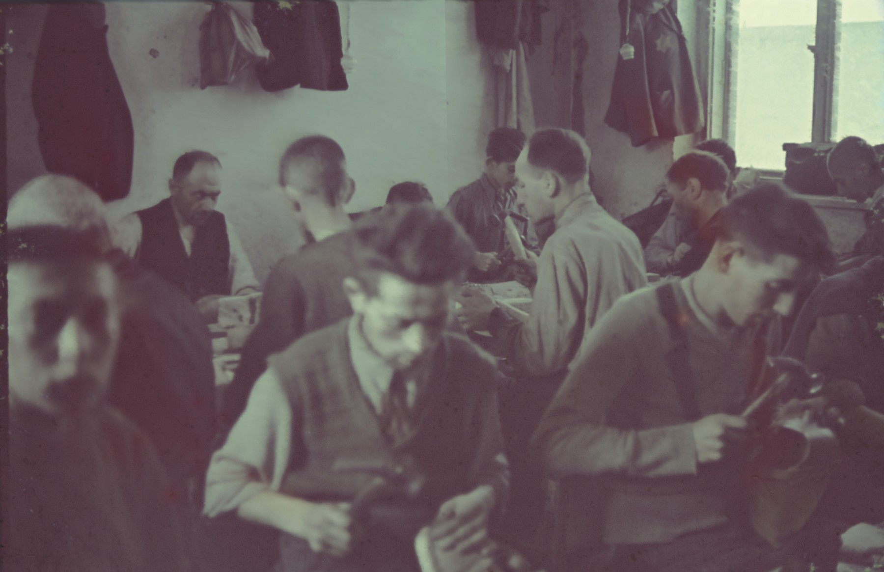 Jewish men at work in a shoemaking workshop.  Original German caption: Litzmannstadt ghetto, Schusterei (shoe-making).