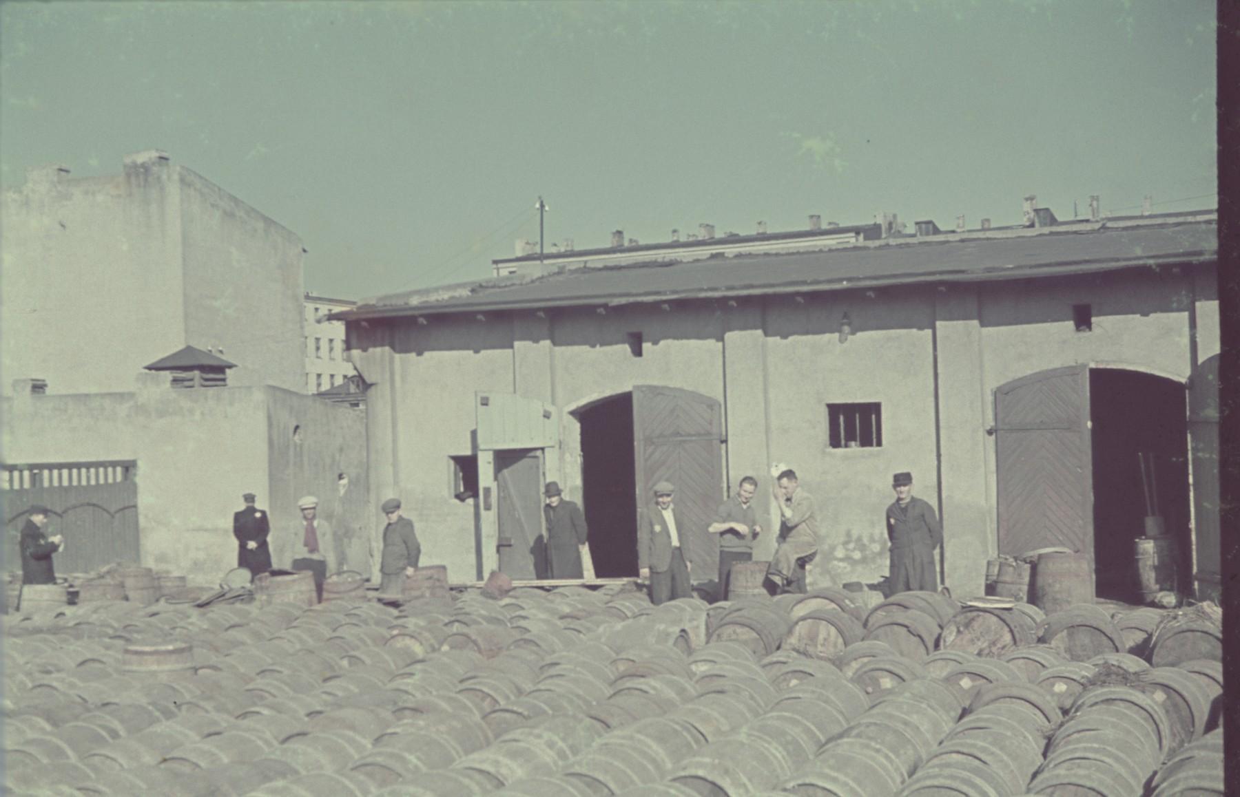 "Jewish workers survey wooden barrels stored in the Lodz ghetto.  Original German caption: ""Lagerplatz"" (warehouse plaza), #145."