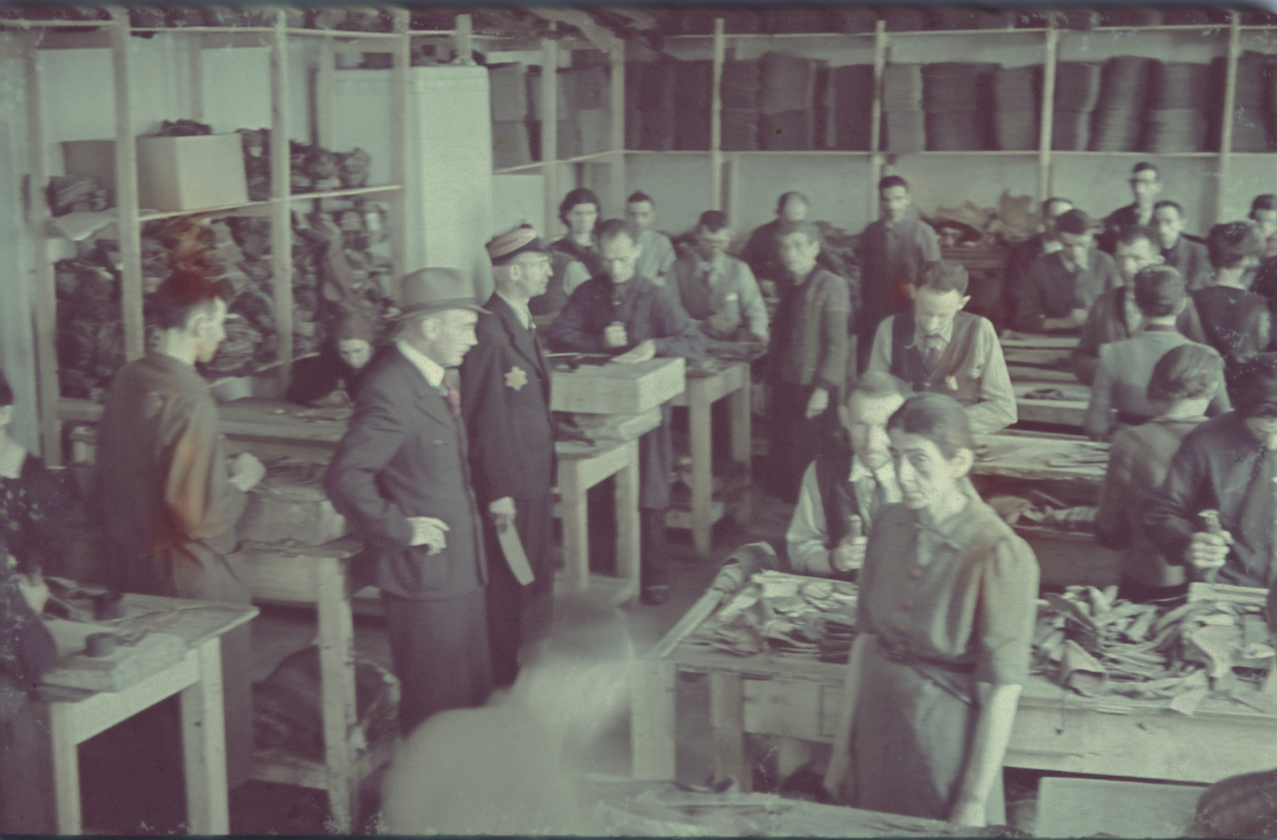 "Workers at the saddle-making workshop stand next to their work tables in the Lodz ghetto.  Original German caption: ""Litzmannstadt-Get, Sattlerei"" (saddlery)."