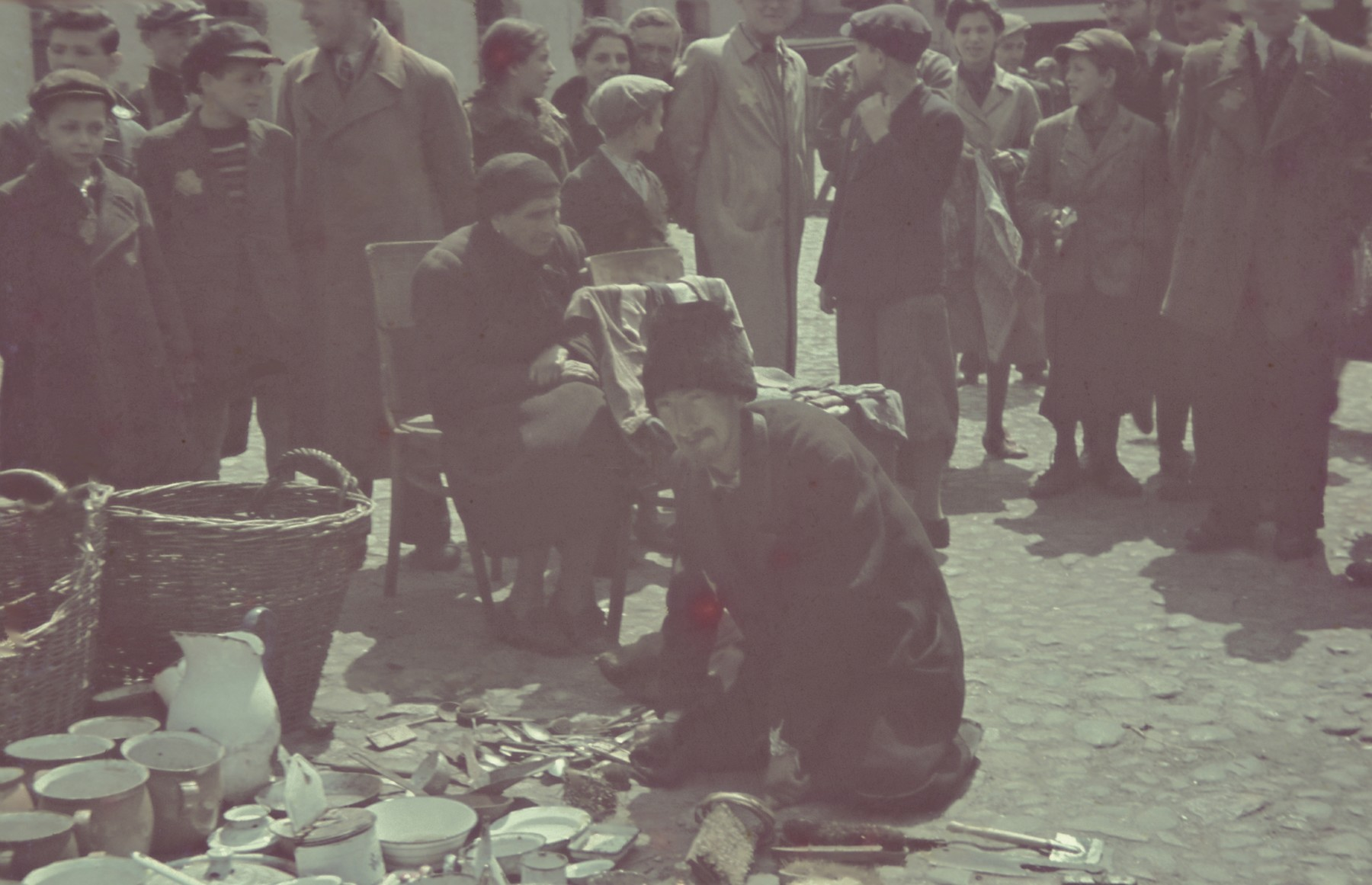 A man sits on the ground next to some used wares he is selling in the outdoor market of the Lodz ghetto.