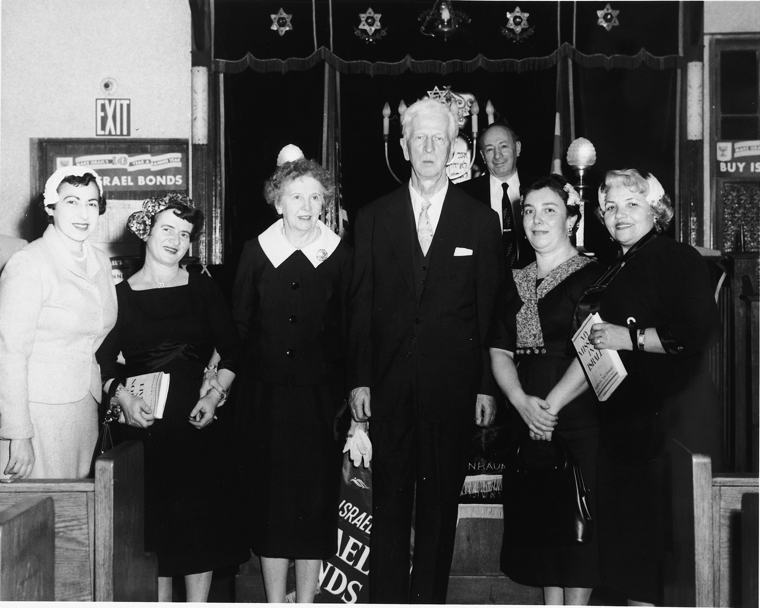 """U.S. Ambassador to Israel James G. McDonald (center) poses with his wife (third from the left) and four other women at a State of Israel bonds drive at a synagogue in the U.S.  Two of the women hold copies of McDonald's 1951 memoir, """"My Mission to Israel."""""""