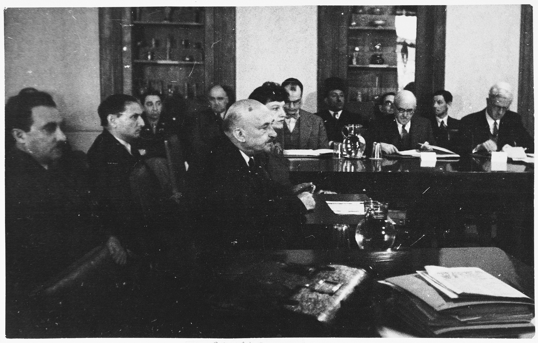 Chaim Weitzmann testifies at a hearing conducted by the Anglo-American Committee of Inquiry on Palestine at the YMCA building in Jerusalem.  Also pictured is James McDonald (far right).