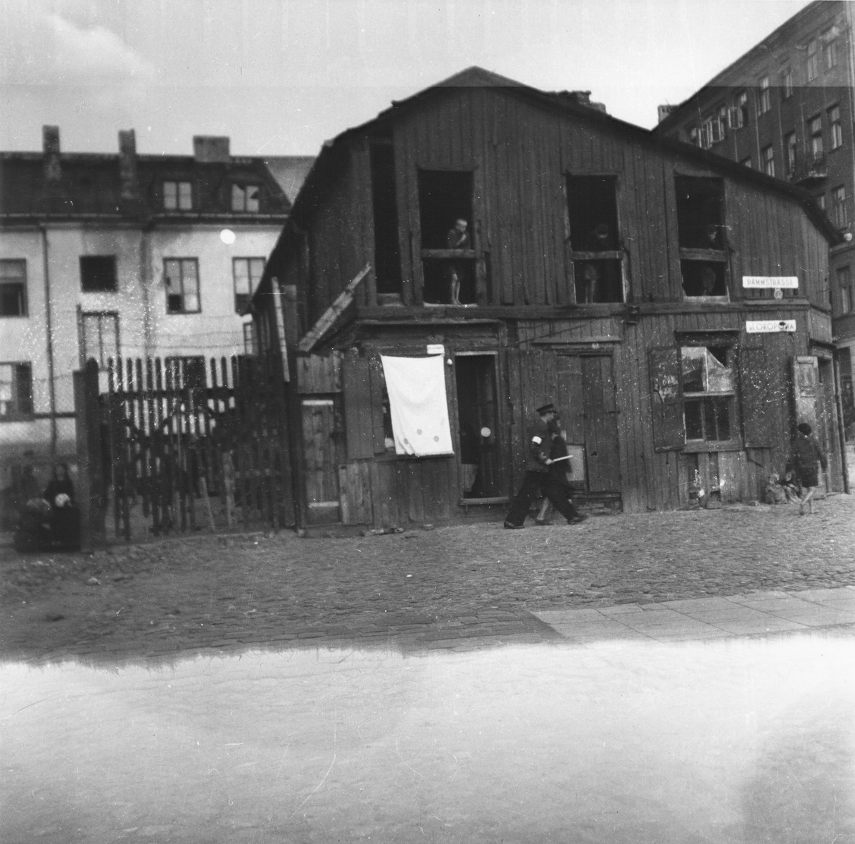 "A Jewish policeman leads away a person he has just arrested in the Warsaw ghetto.    Joest's caption reads: ""A Jewish auxiliary policeman had arrested someone and was taking him away, probably a smuggler.  This picture was taken on the Okopawa.  At that time it was called Dammstrasse and was the border between the Ghetto and the cemetery."""