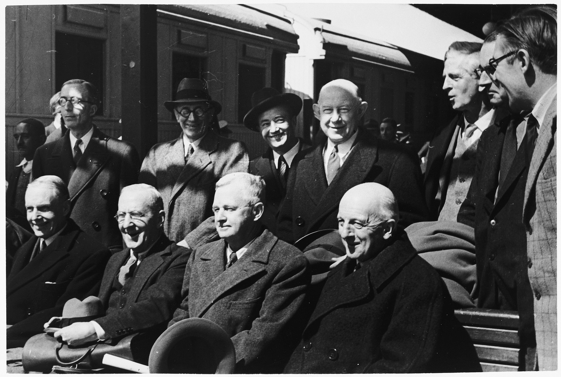 Group portrait of members of the Anglo-American Committee of Inquiry on Palestine after their arrival at the train station in Jerusalem.  Pictured seated from right to left are: Judge Joseph Hutcheson (American chairman), Frank Singleton (British chairman), Frank Buxton (U.S.), and William Phillips (U.S.).  Standing from right to left are: R.H.S. Crossman (UK), R.E. Manningham-Buller (UK), James G. McDonald (U.S.), Frank Aydelotte (U.S.), Bartley Crum (U.S.), Sir Frederick Leggett (UK), and W.F. Crick (UK).  The twelfth member of the committee was Lord Morrison (UK).
