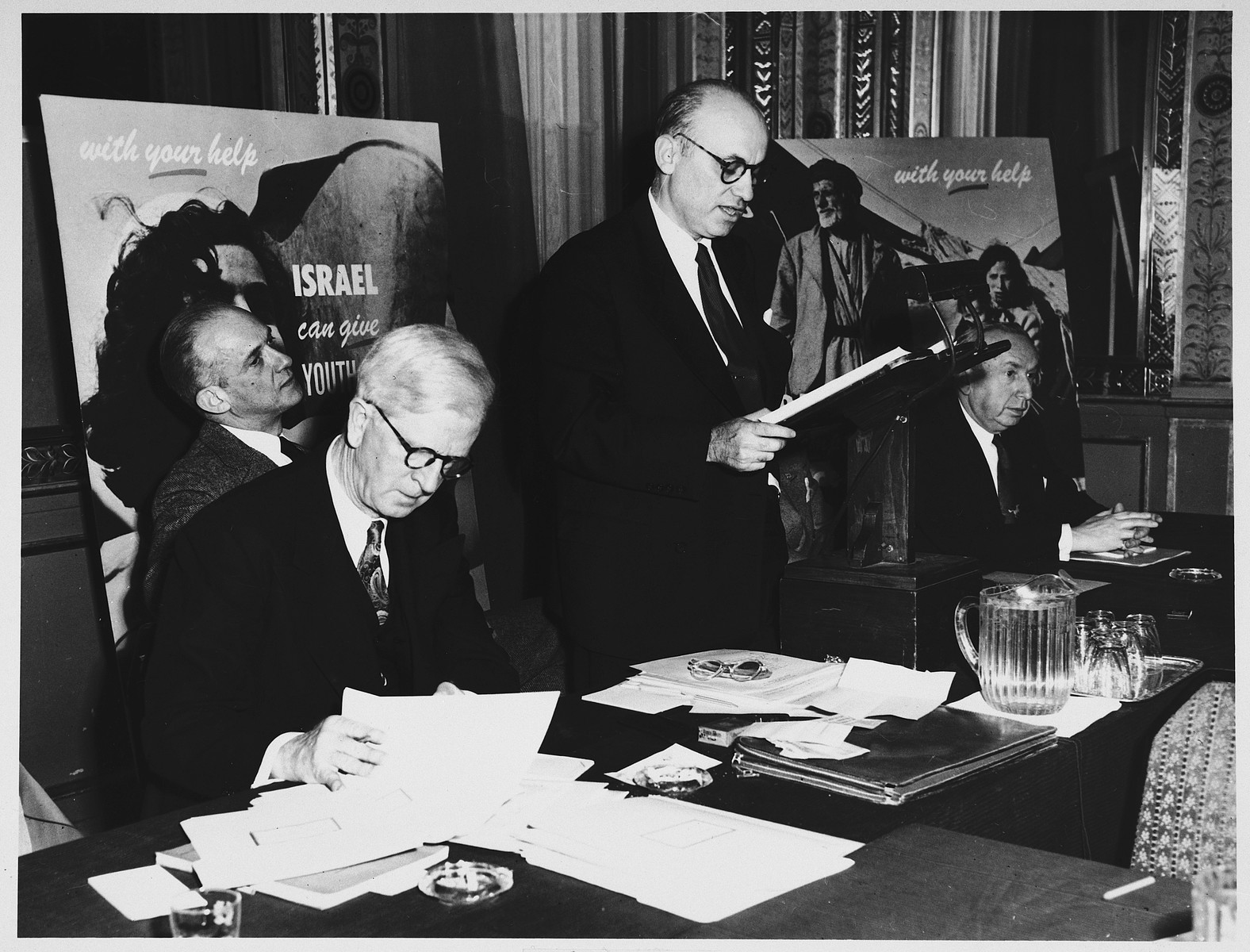 James G. McDonald (seated, left), Chairman of the Advisory Council, Development Corporation for Israel, looks through his papers while attending a conference about fundraising for the State of Israel.