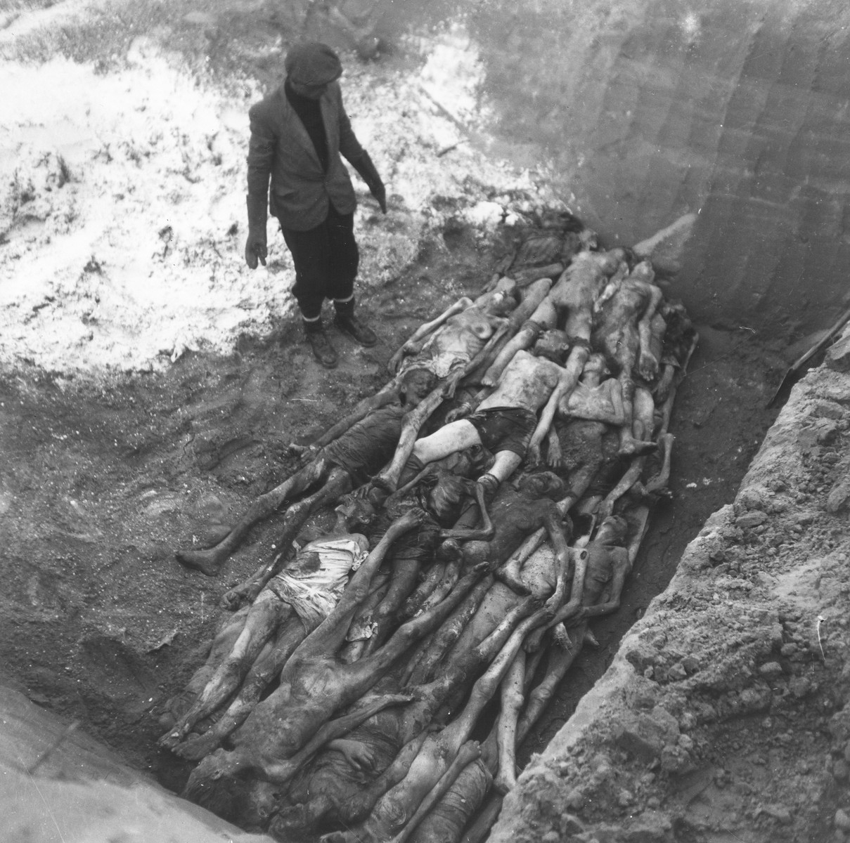 """An undertaker views a layer of corpses laid out at the bottom of a mass grave in the Okopowa Street cemetery.    Joest's caption reads: """"Once again a layer of the dead was finished and now had to be covered with lime.  I couldn't believe one pit could have space for so many people."""""""