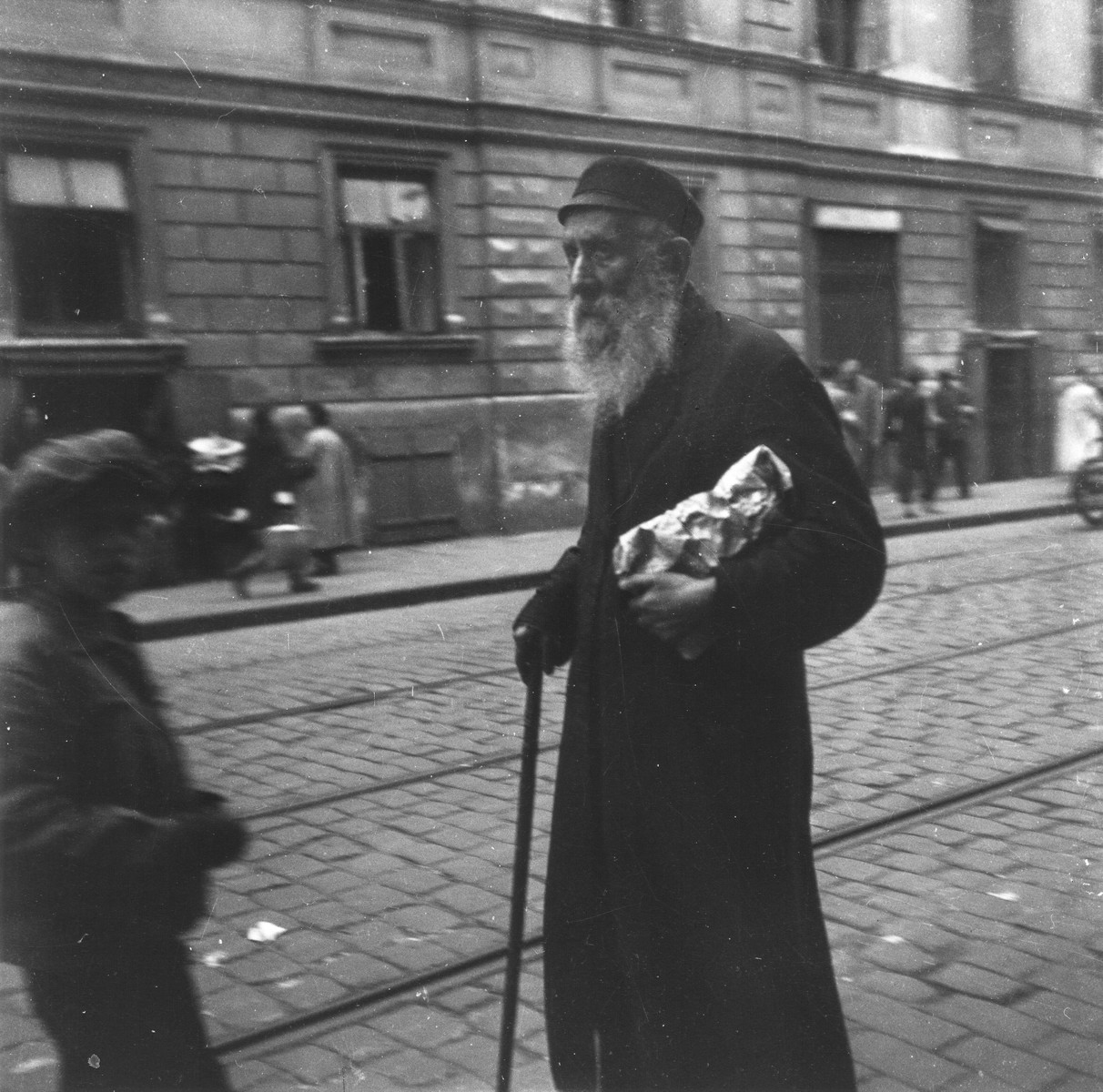 """An elderly Jew holding a package and a cane walks along a commercial street in the Warsaw ghetto.    Joest's original caption reads: """"It struck me like an image out of the Old Testament--this old man with a small bundle in his arm, walking towards certain death."""""""