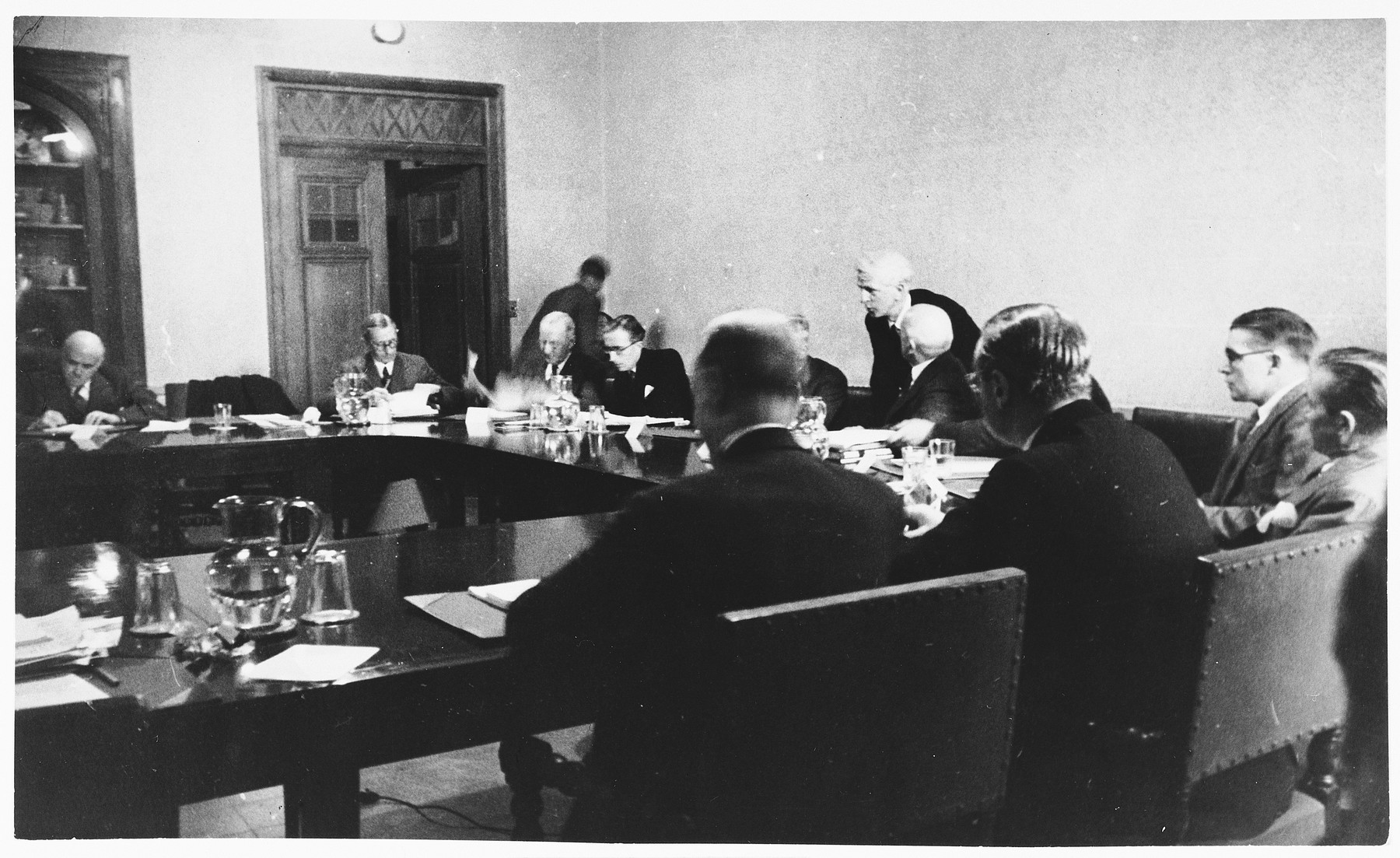 James McDonald converses with committee members at a hearing conducted by the Anglo-American Committee of Inquiry on Palestine at the YMCA building in Jerusalem.
