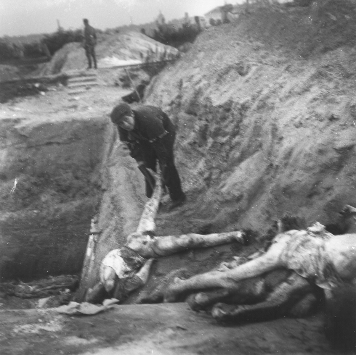 """A boy working in the Warsaw ghetto cemetery drags a corpse to the edge of the mass grave where it will be buried.    Joest's caption reads: """"The boy slid the dead over the edge into the pit.  A German soldier was standing in the background, watching."""""""