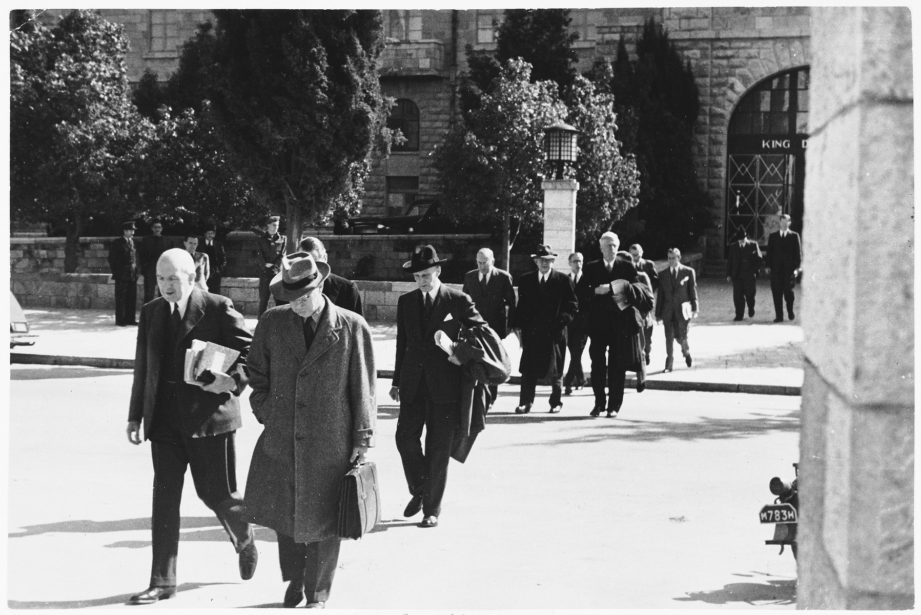Members of the Anglo-American Committee of Inquiry on Palestine walk across the street from their lodgings at the King David Hotel to the YMCA building, where they are holding hearings about the situation in Palestine.  Among those pictured is James G. McDonald (the tall man near the lamp post).