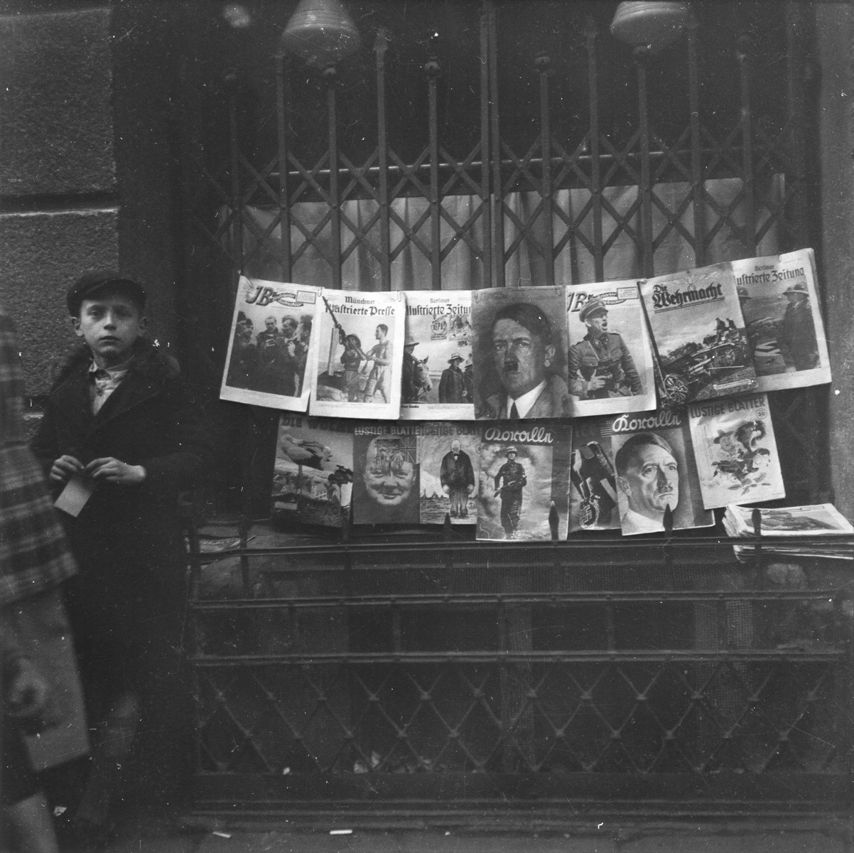 """A young boy sells German Nazi periodicals on a street in the Warsaw ghetto.    Joest's original caption reads: """"This boy was even trying to make money selling old German newspapers with pictures of Hitler.  While I was looking, no one bought anything from him."""""""
