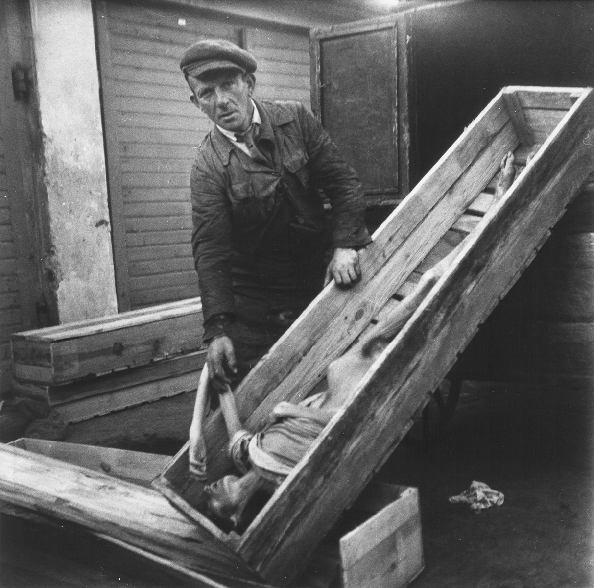 "An undertaker in the Warsaw ghetto cemetery on Okopowa Street displays an open coffin that contains the body of woman.    Joest's caption reads: ""He pulled out a second box with a dead woman, an old one.  She was still wearing a blouse."""