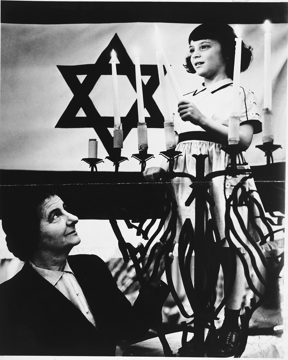 Golda Meir watches as a young girl lights a menorah during an official Hanukkah candlelighting ceremony in Israel.