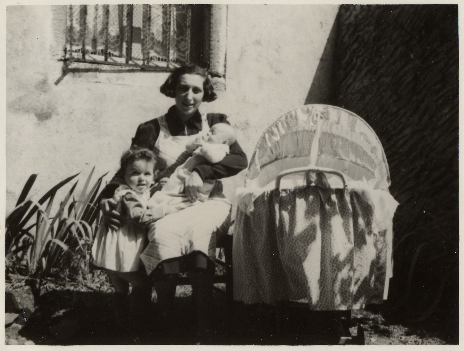 Portrait of a woman with her two small children posing in front of a house.   Pictured is Tonia Lechtman with her children Vera and Marcel.