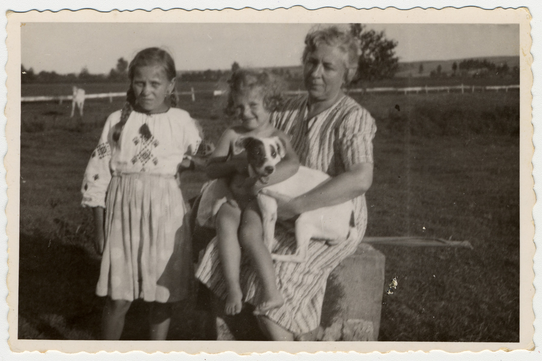 A young Jewish girl in hiding sits on the lap of her rescuer in a farm in eastern Poland while an older Jewish girl in hiding stands next to them.  Pictured is Emanuella (Illa) Kitz.