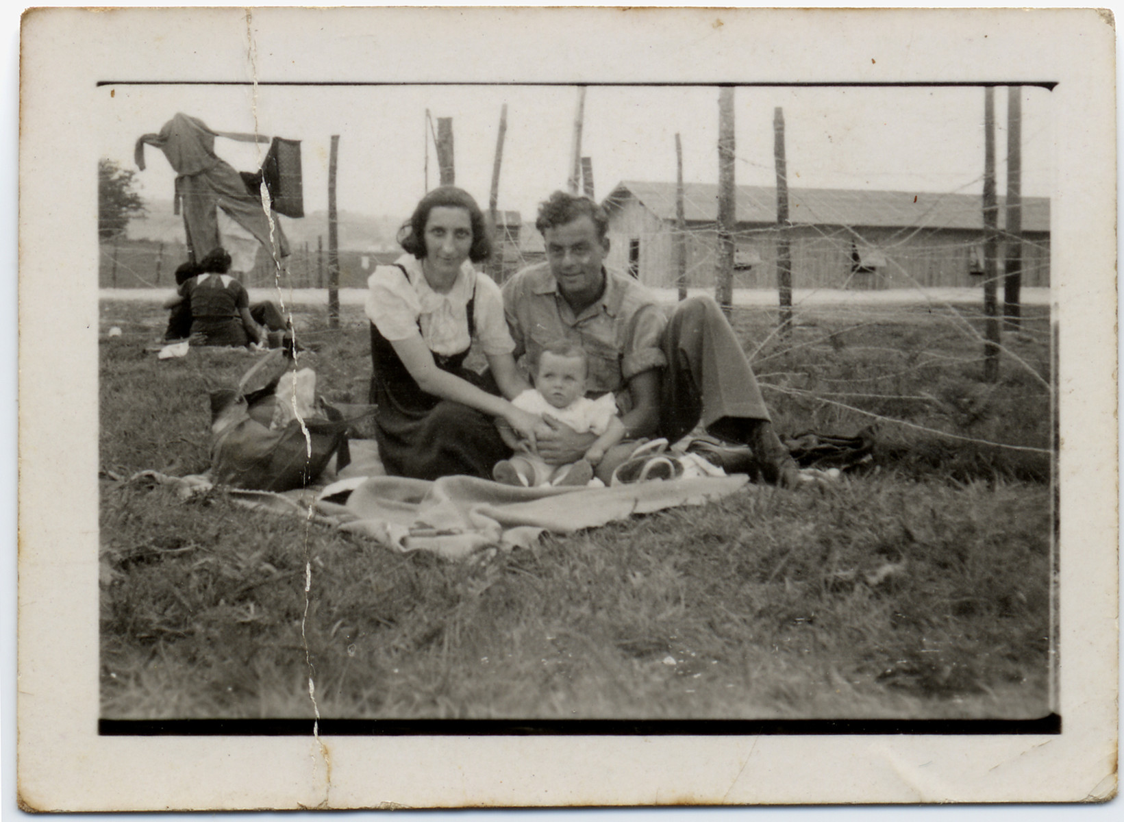 A couple with their young child sits on the grass near the barbed wire fence of the Gurs internment camp.   Pictured are Tonia and Sioma Lechtman with their baby Vera.