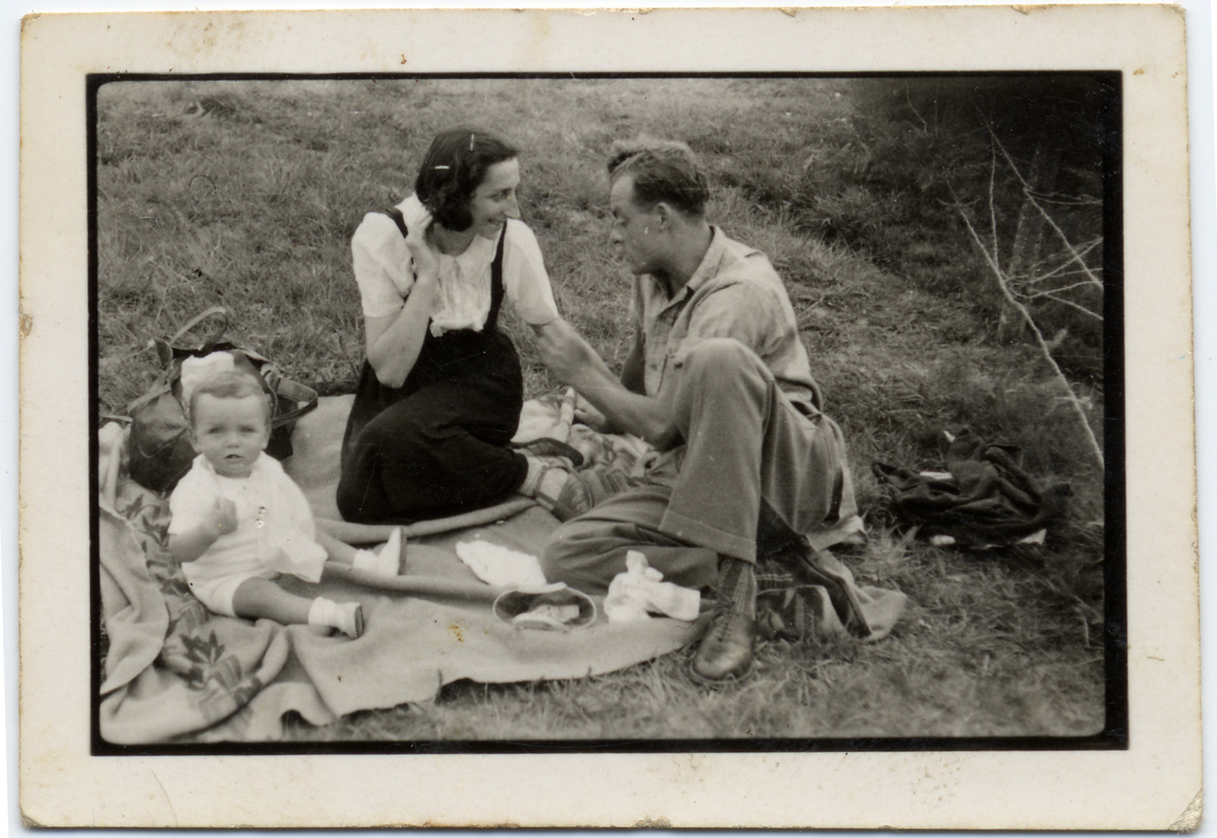 A couple with their young child sits on the grass on an open field in the Gurs internment camp.   Pictured are Tonia and Sioma Lechtman with their baby Vera.