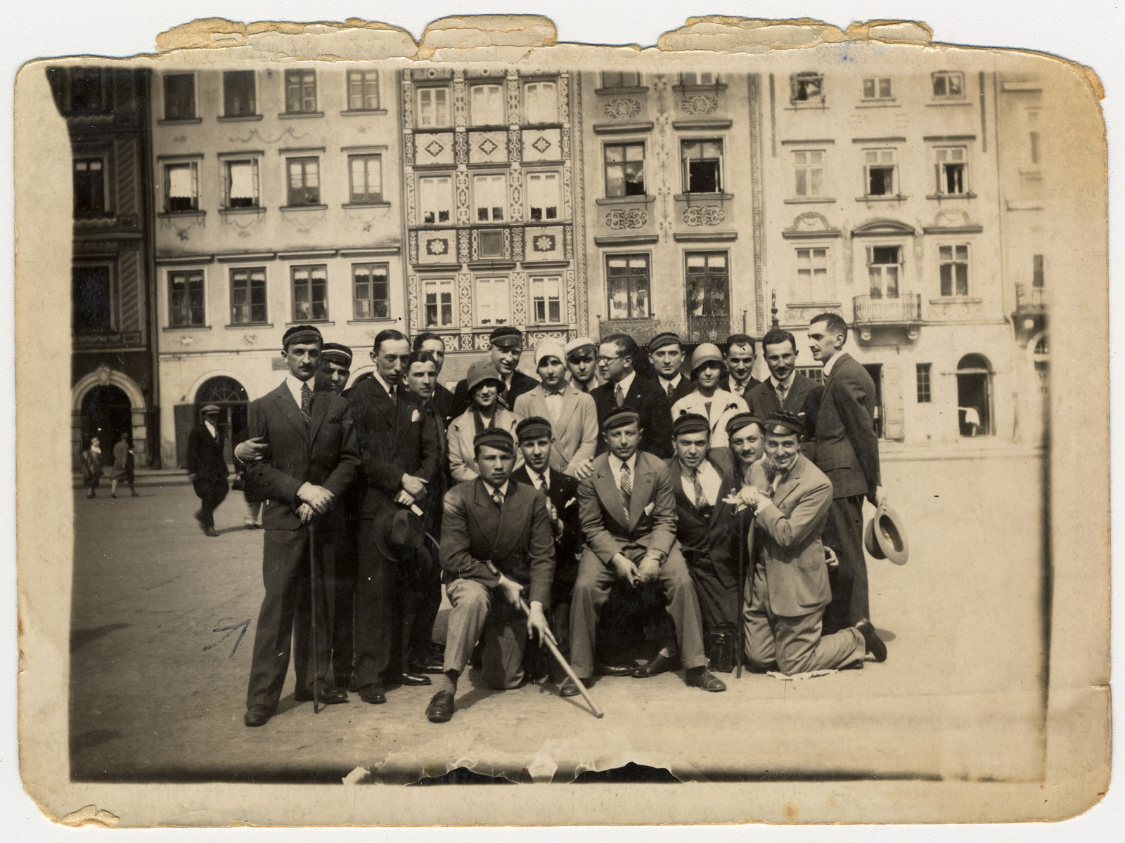 A group of friends, many of whom are wearing university caps, pose for a group portrait on a street in Warsaw.  Among those pictured is Henryk Rothard (far left), the step-father of the donor.