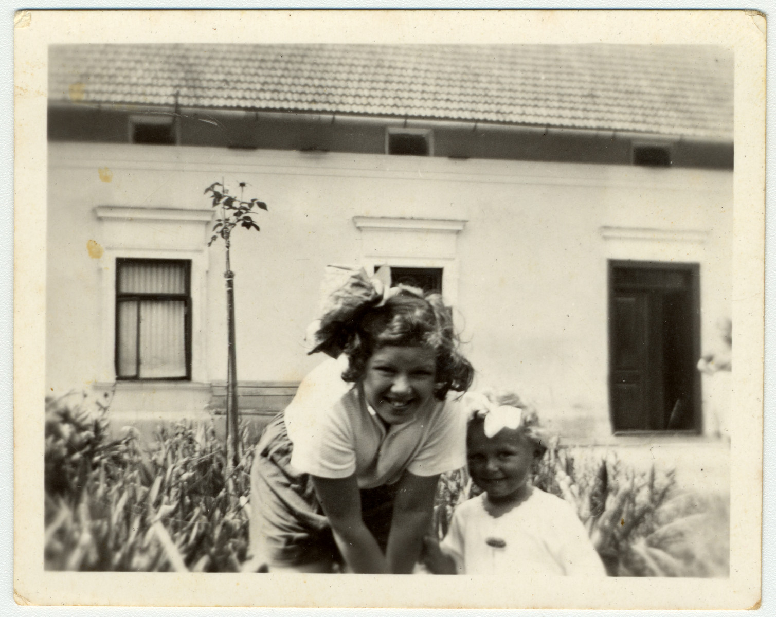 Close-up portrait of two Jewish children outside in the yard outside a building in Kniaze.