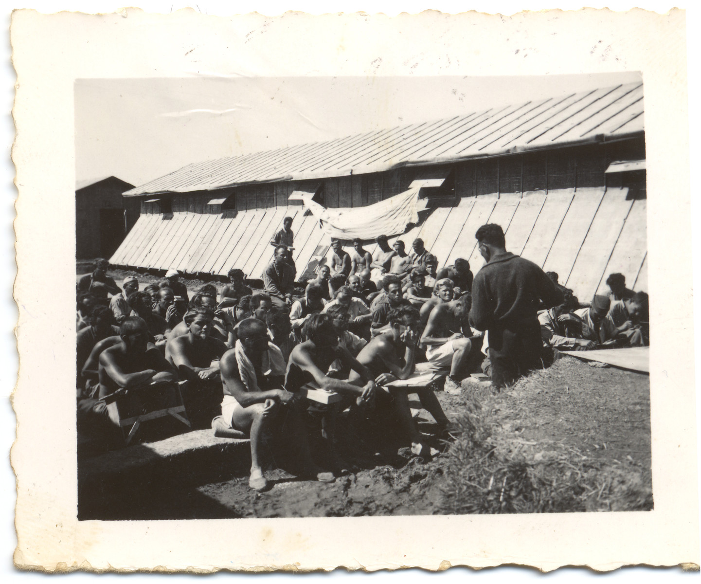 Prisoners [possibly members of the International Brigade who fought in the Spanish Civil war] listen to a speaker in the Gurs internment camp.   The donor's father might be the man sitting on the far right and taking notes.