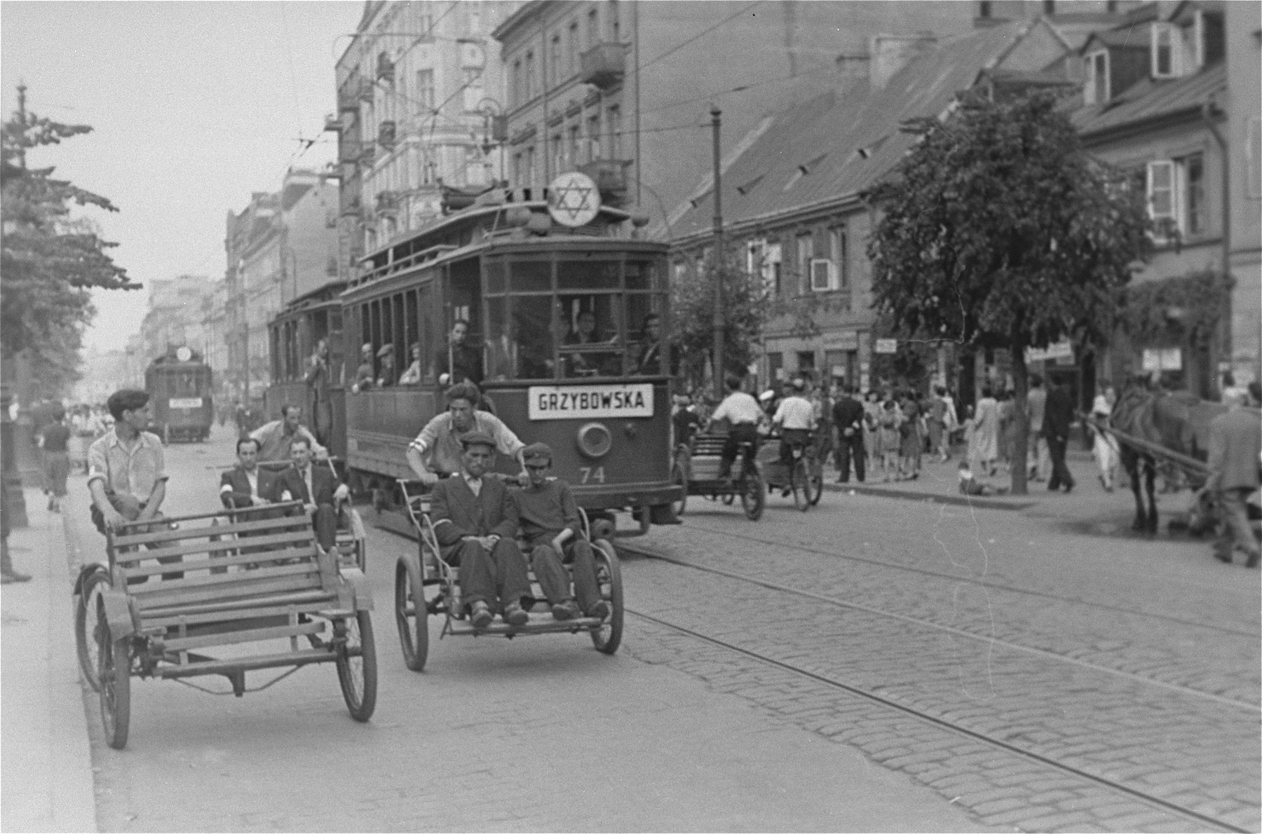 Rickshaws and streetcars move through a major street in the Warsaw ghetto.
