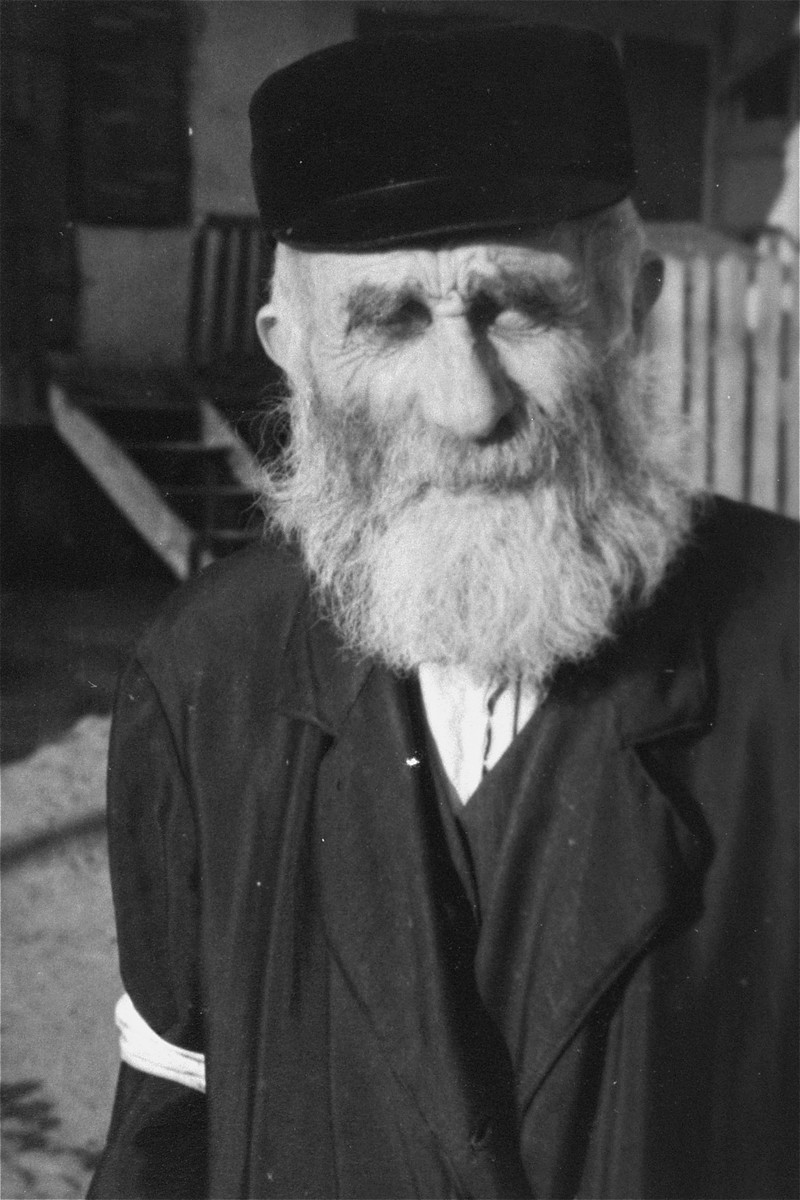 Portrait of an elderly religious Jew wearing an armband in an unidentified ghetto.