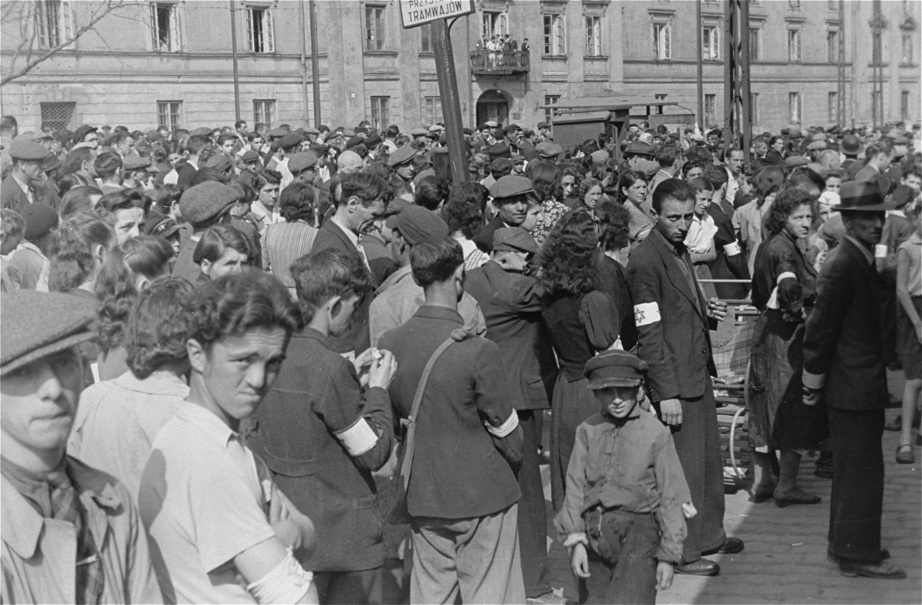 Jews gathered on the plaza at Zamenhofa and Nowolipki Streets in the Warsaw ghetto listen to an announcement on the public address system.