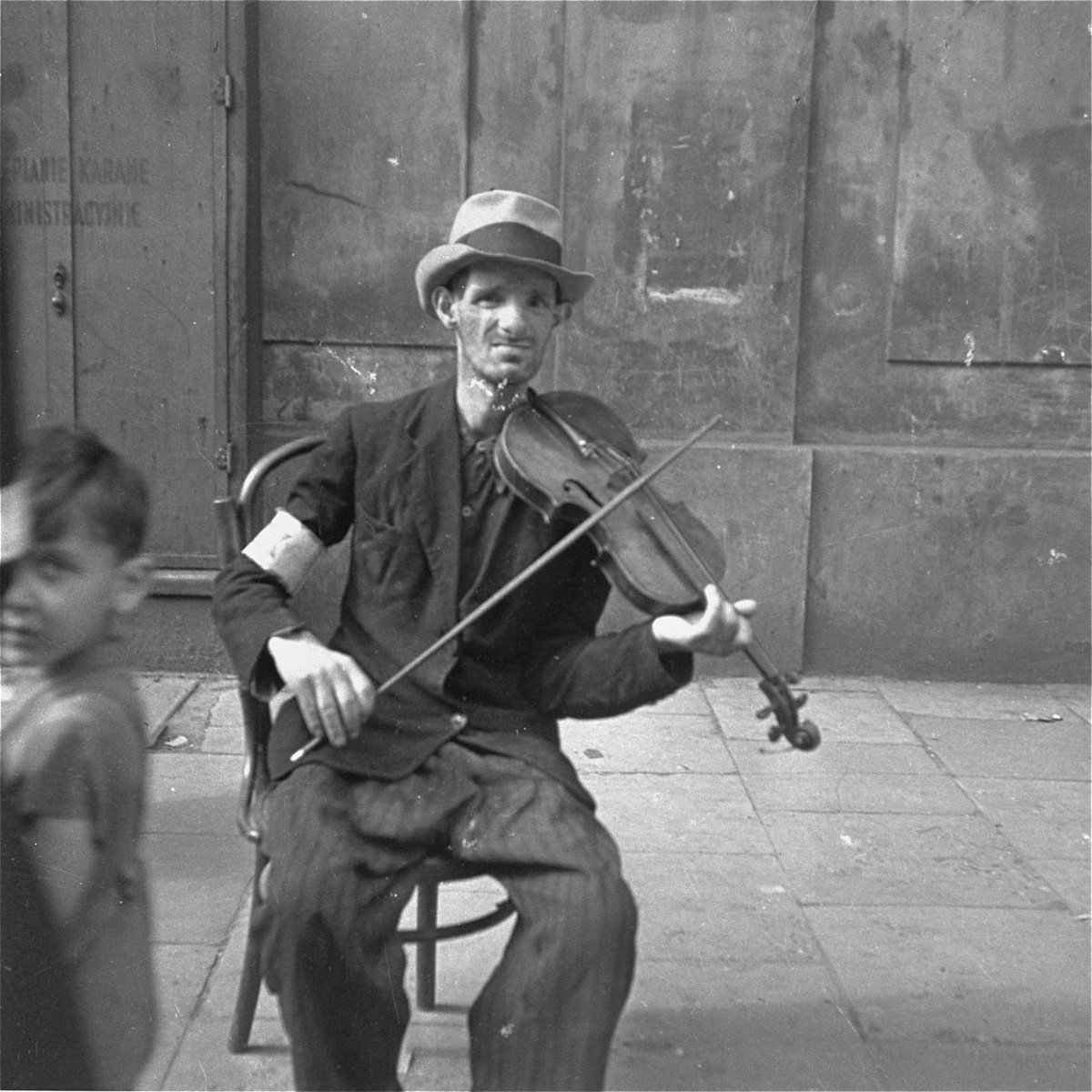 """A man on the street plays the violin in the hope of receiving food or money.    Joest's original caption reads:  """"This man played the same sound on his violin again and again.  His eyes followed me, but whether out of fear or because he hoped to receive a coin I do not know."""""""