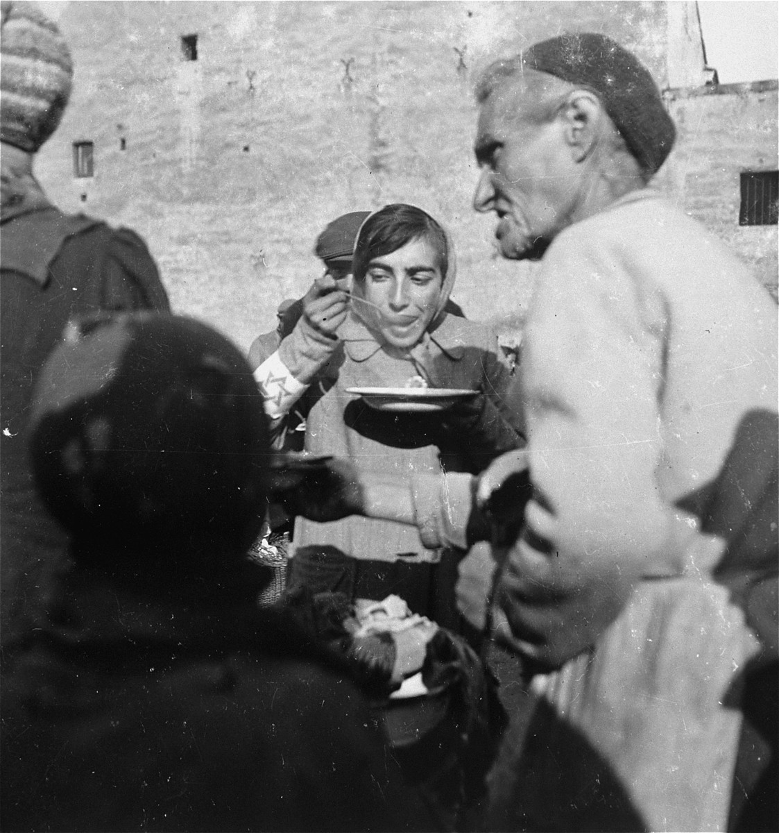 "A woman in the Warsaw ghetto eats soup she received from a public kitchen.    Joest's original caption reads: ""Food from a large tureen was given out to Jews who waited there in a long line.  The woman in the foreground stood in the line and held out her bowl.  The woman behind her ate her thin soup from a lead bowl."""