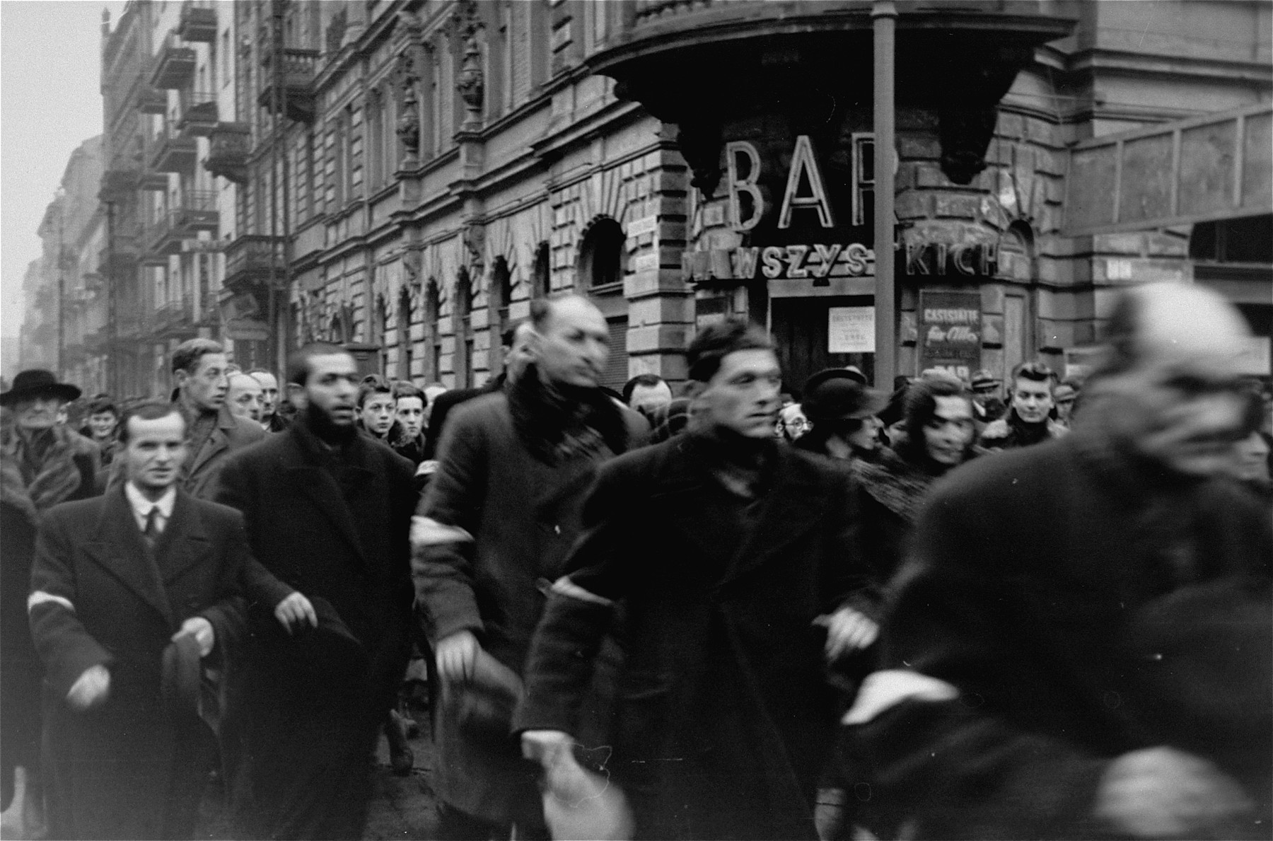 Jews crossing the intersection of Zelazna and Chlodna streets in the Warsaw ghetto doff their hats to the photographer, in accordance with the German order requiring Jews to remove their hats in the presence of German personnel.