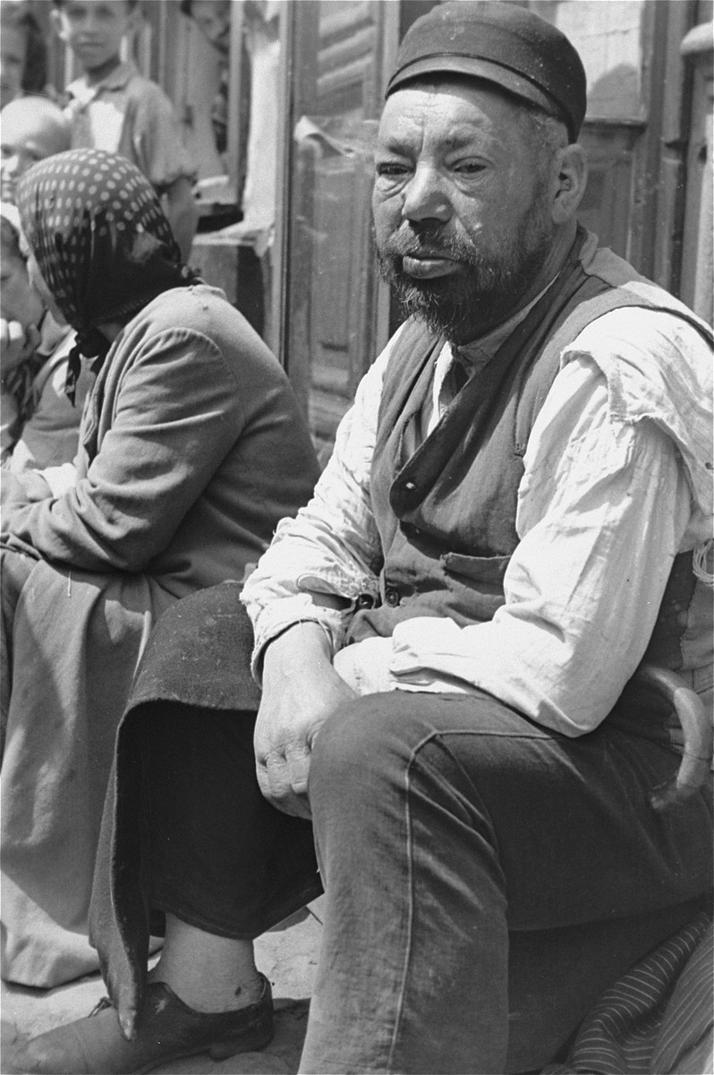 Portrait of a Jewish man sitting on a stoop in the Warsaw ghetto.