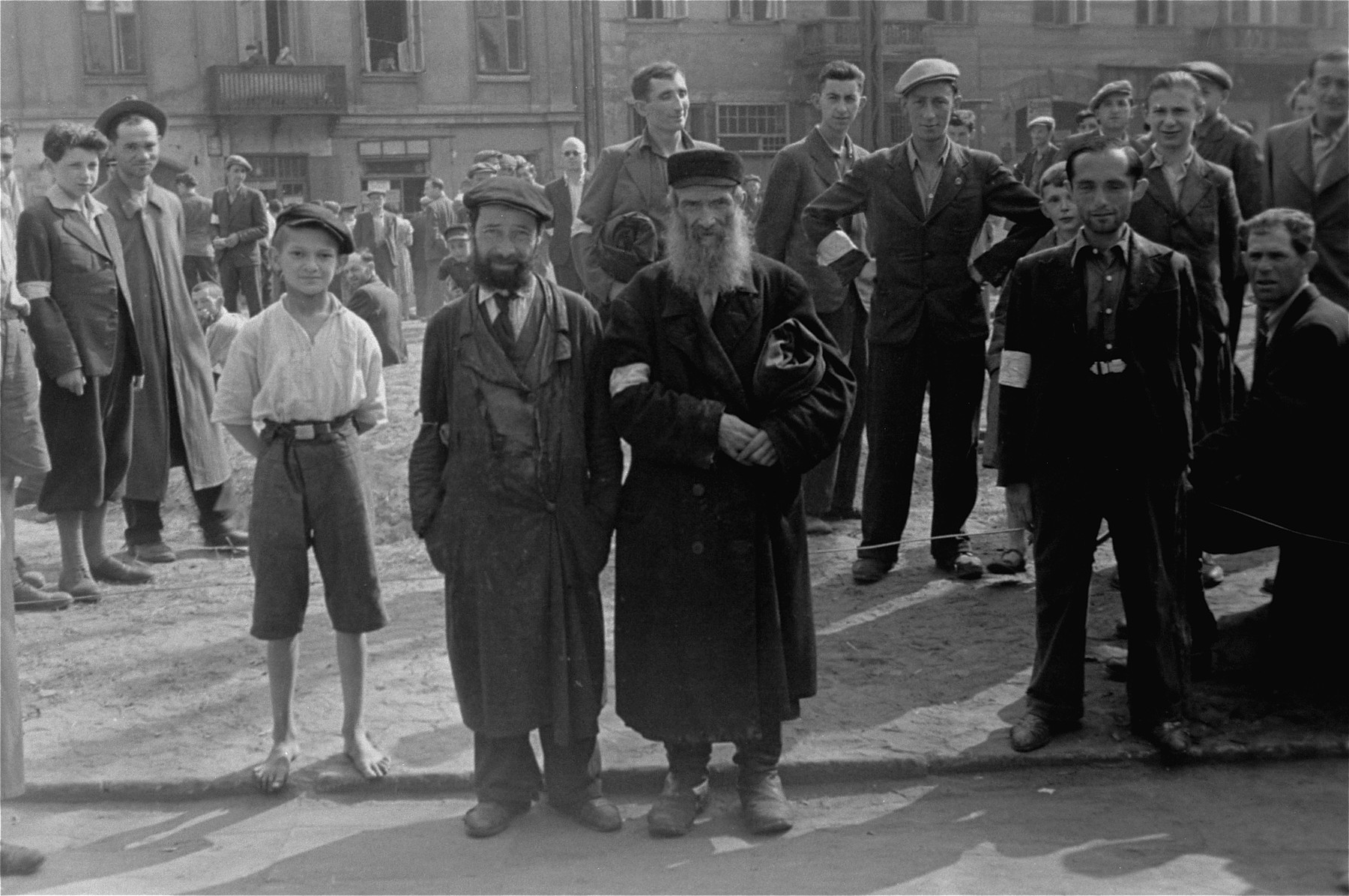 Jewish men and youth are gathered in an open area in the Warsaw ghetto.