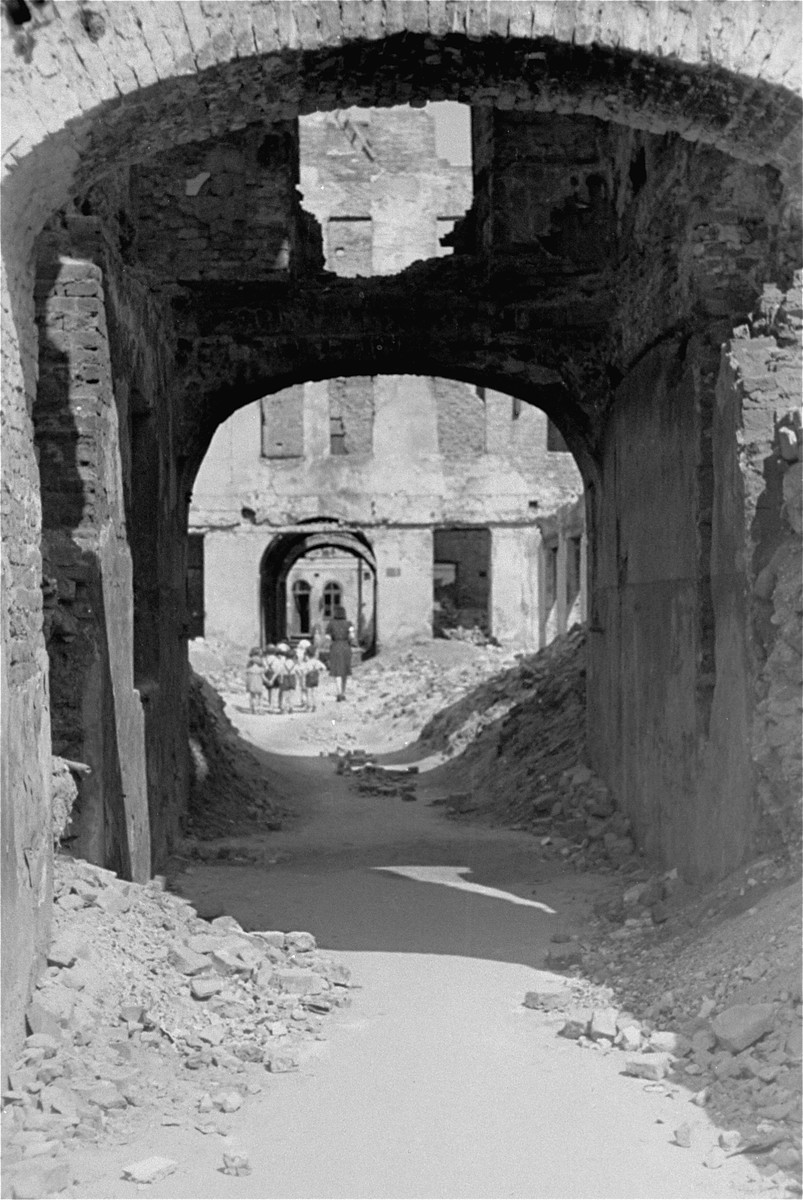 A woman escorts a group of children through a series of arches on a rubble-strewn street in the Warsaw ghetto.