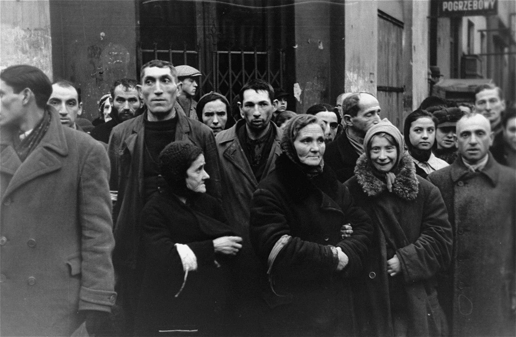 Jewish men standing among a crowd of people on a street in the Warsaw ghetto, doff their hats to the photographer, in accordance with the German order requiring Jews to remove their hats in the presence of German personnel.