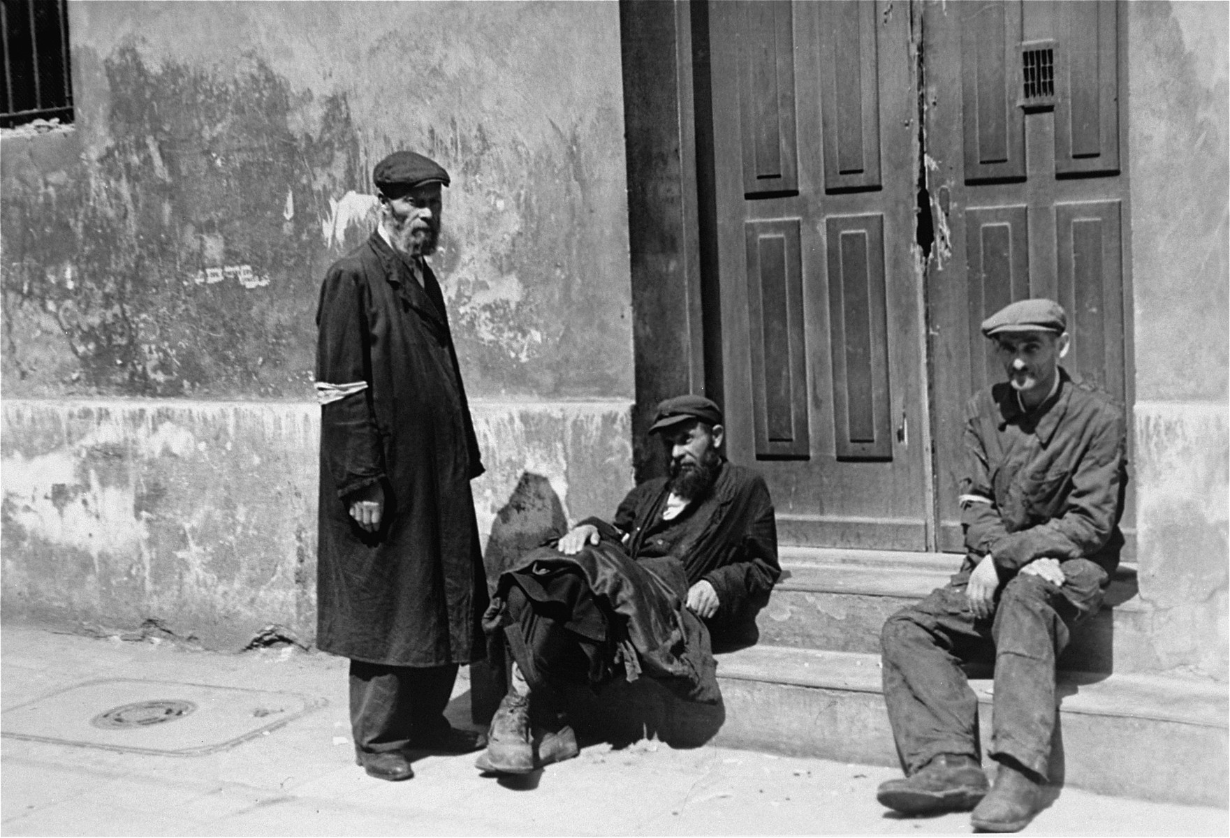 Three Jewish men sit outside the entrance to a building in the Warsaw ghetto.