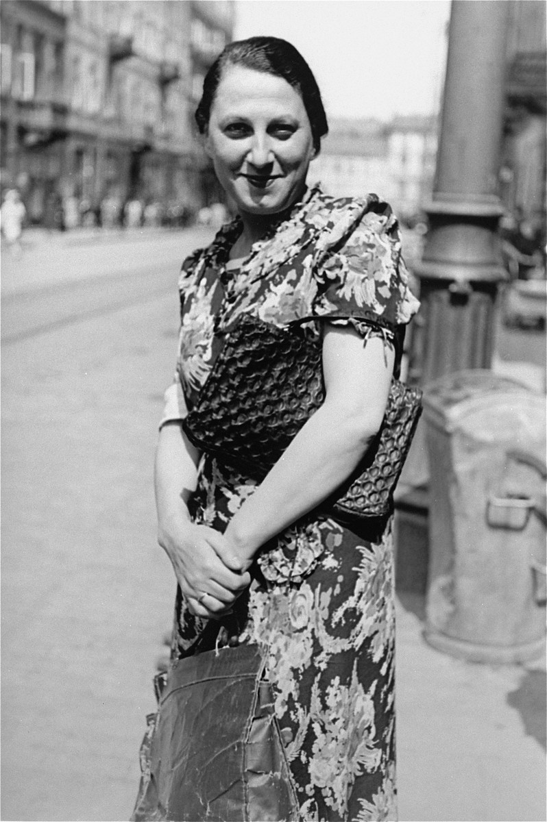 Portrait of a well-dressed Jewish woman clutching a purse on a street in the Warsaw ghetto.