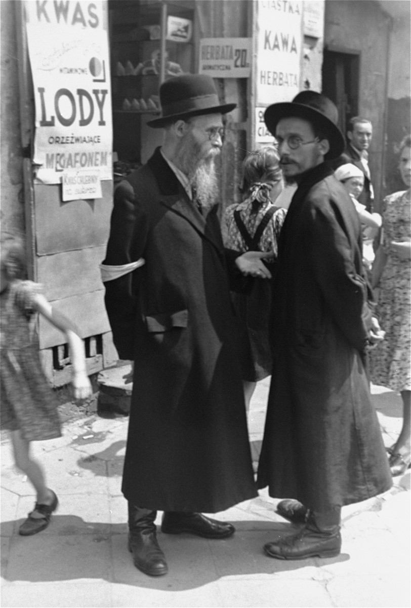 Religious Jews converse on a busy street in the Warsaw ghetto.