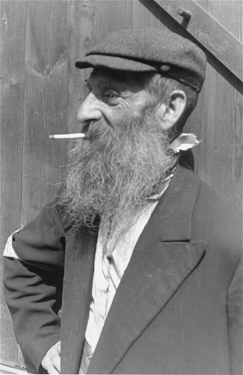 Portrait of a bearded Jewish man smoking a cigarette in the Warsaw ghetto.