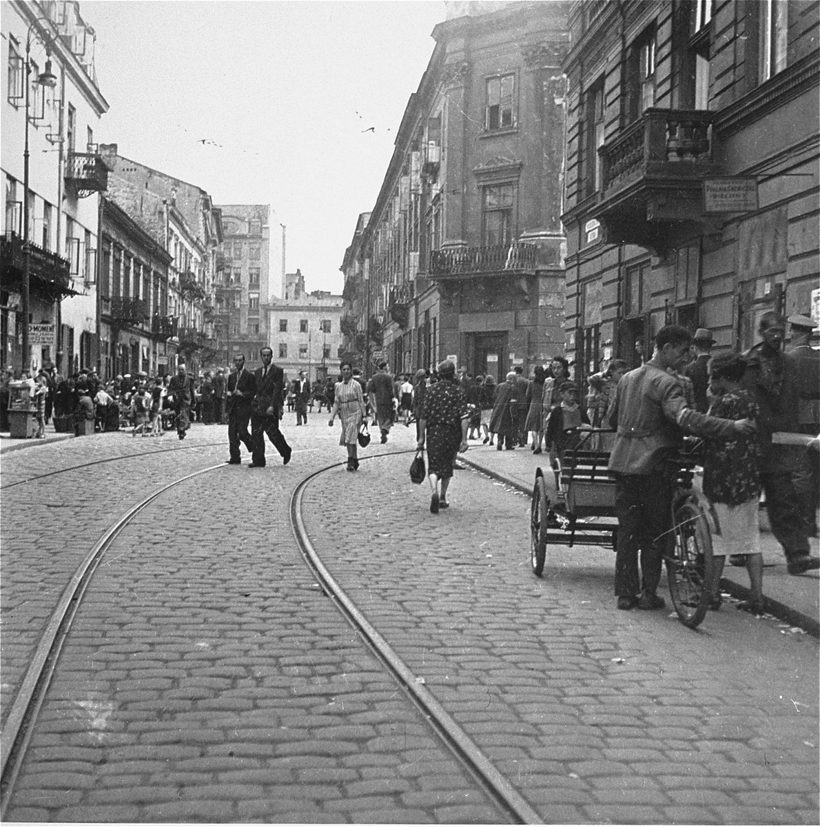 "Jews on Nowolipki Street in the Warsaw ghetto.  At far right a German army sergeant (Feldwebel) can be seen walking down the street.    Joest's caption reads: ""I saw vendors, rickshaw drivers, passersby, and a German sergeant on Nowolipki Street."""