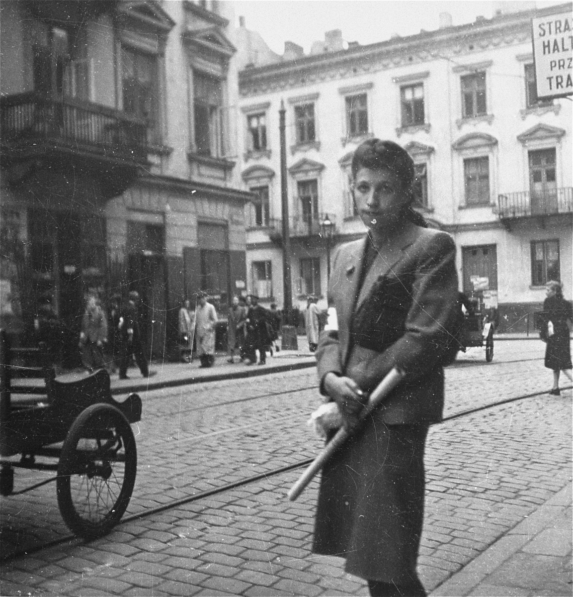 "A well-dressed woman poses on a commercial street in the Warsaw ghetto.    Joest's original caption reads: ""She looked cultivated, this lady in fancy dress with a purse under her arm and a roll of paper in her hand.  I do not know what I thought at that time: may I actually photograph you?  Strangely enough I did not think this when I saw poorly dressed people."""