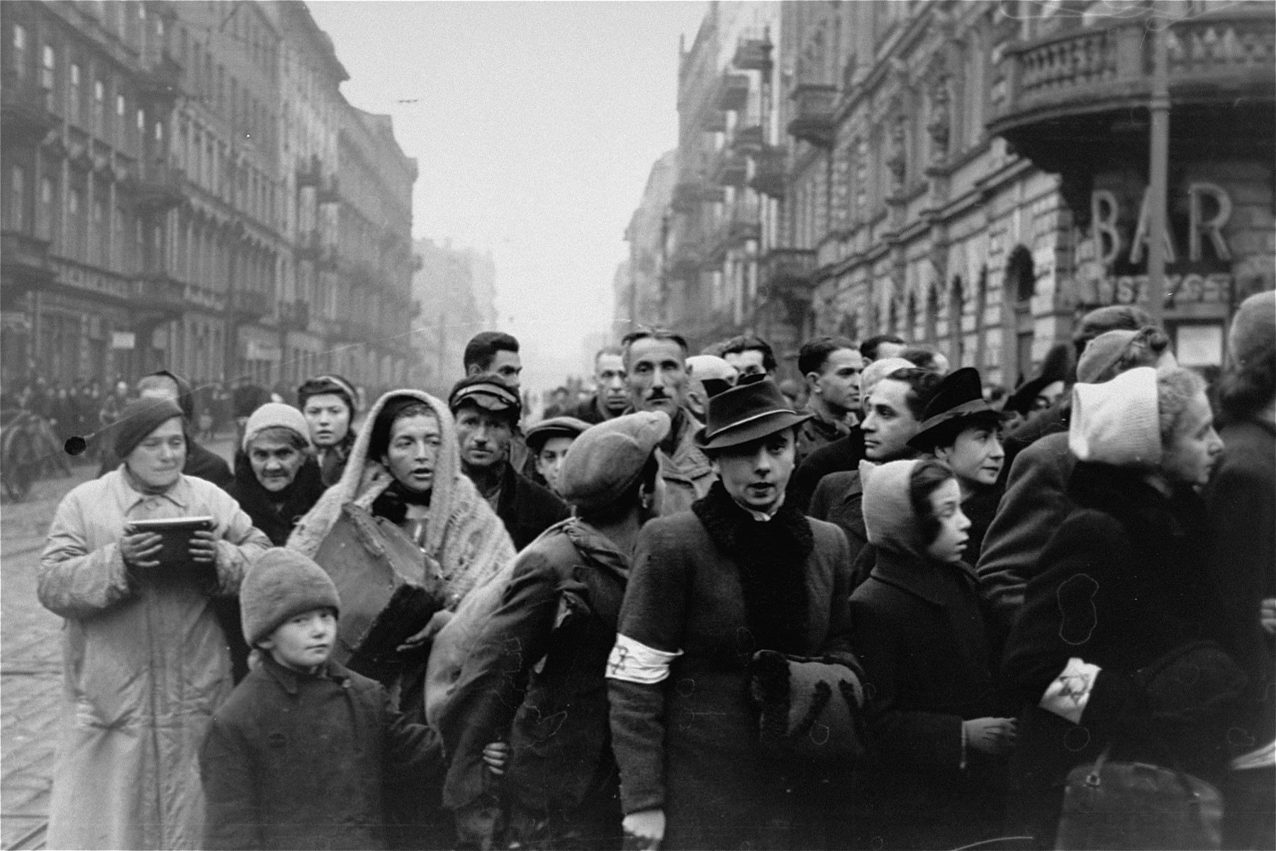 Jews are gathered at the intersection of Karmelicka and Nowolipki Streets in the Warsaw ghetto.